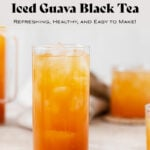 Iced Guava Black Tea shown in a tall glass with ice on beige background. More glasses and a jug full of iced tea partially in the frame on both left and right. Beige tea towel blurry in the background.