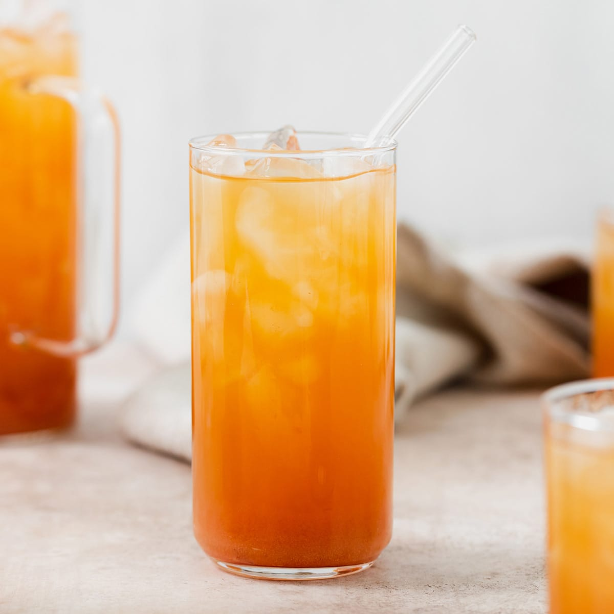Iced Guava Black Tea shown in a tall glass with ice and a glass straw on beige background. More glasses and a jug full of iced tea partially in the frame on both left and right. Beige tea towel blurry in the background.