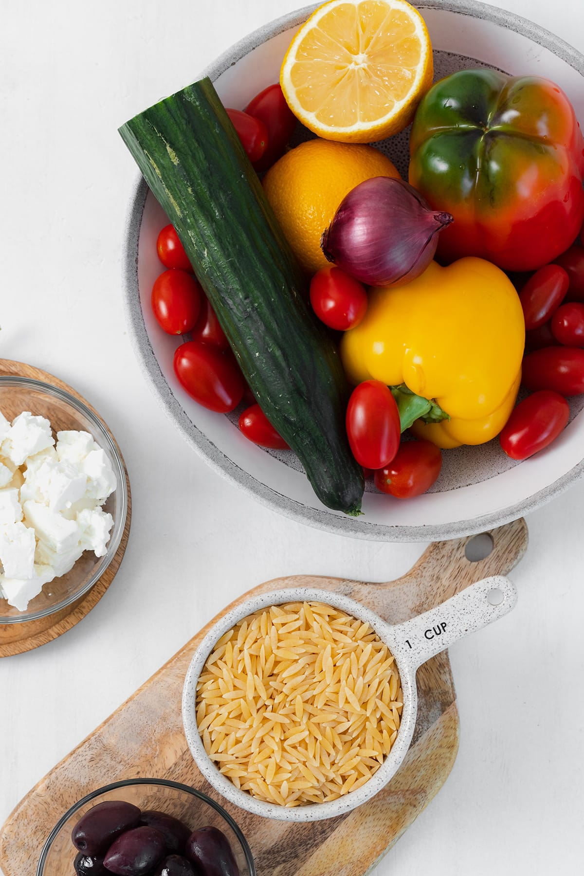 Ingredients for the orzo salad shown laid out on a white background. Cucumber, tomatoes, bell peppers, lemons, feta cheese, orzo, and red onion.