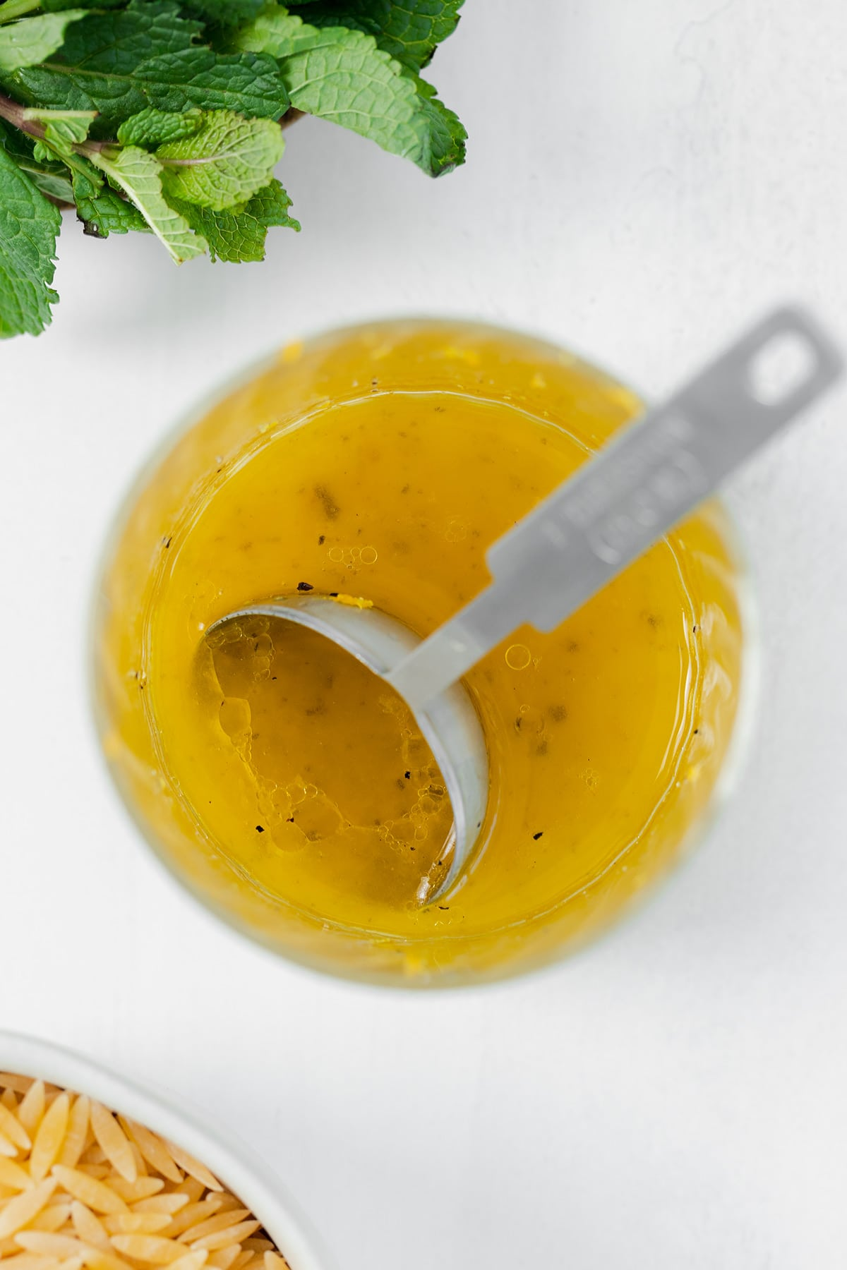 Lemon vinaigrette in a small glass with a measuring spoon in it. On a white background with fresh mint in the top left corner and dry orzo in the bottom left corner.