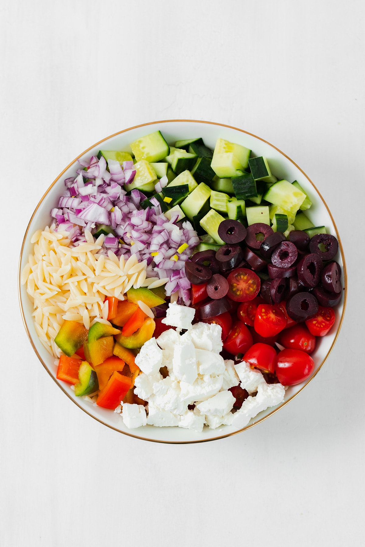 All the ingredients for the orzo salad chopped and laid out in a white bowl with a gold rim.