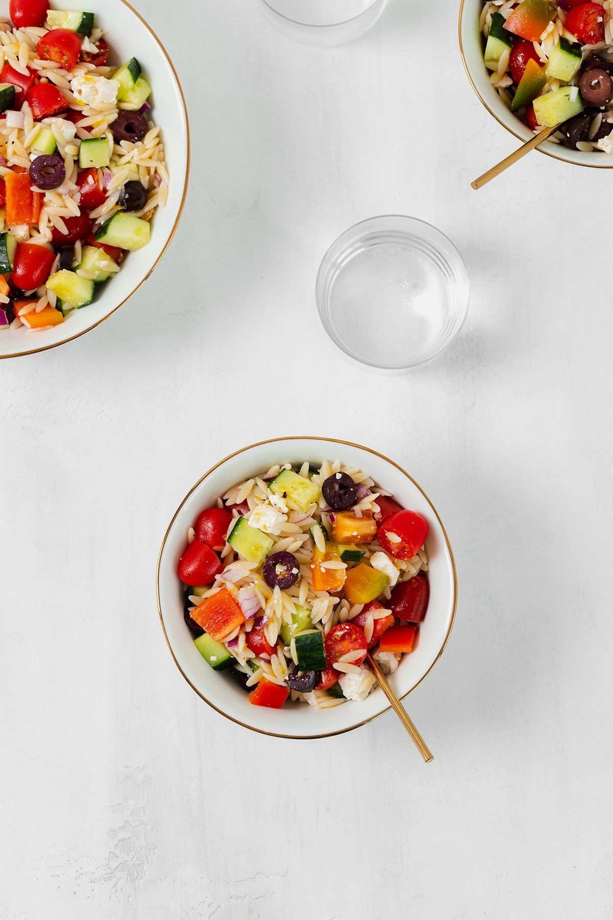 Orzo salad shown in a small white bowl with a gold rim. A small glass of water in the right side above it. Partially shown bigger bowl on the top left corner and a smaller bowl in the top right corner. Both bowls have the pasta salad in them.