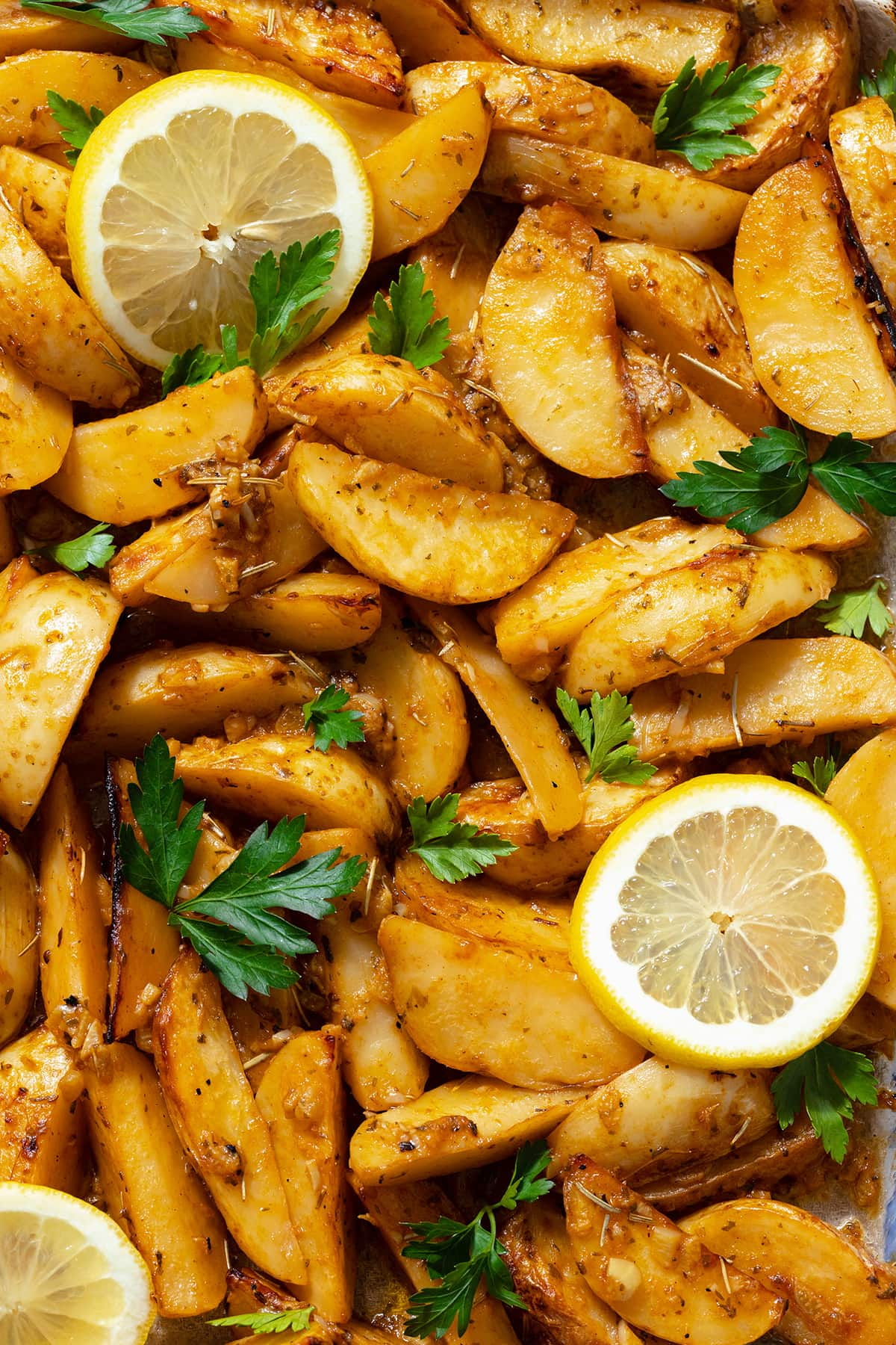 A close up photo of Mediterranean Potatoes garnished with three slice of lemon and chopped parsley.
