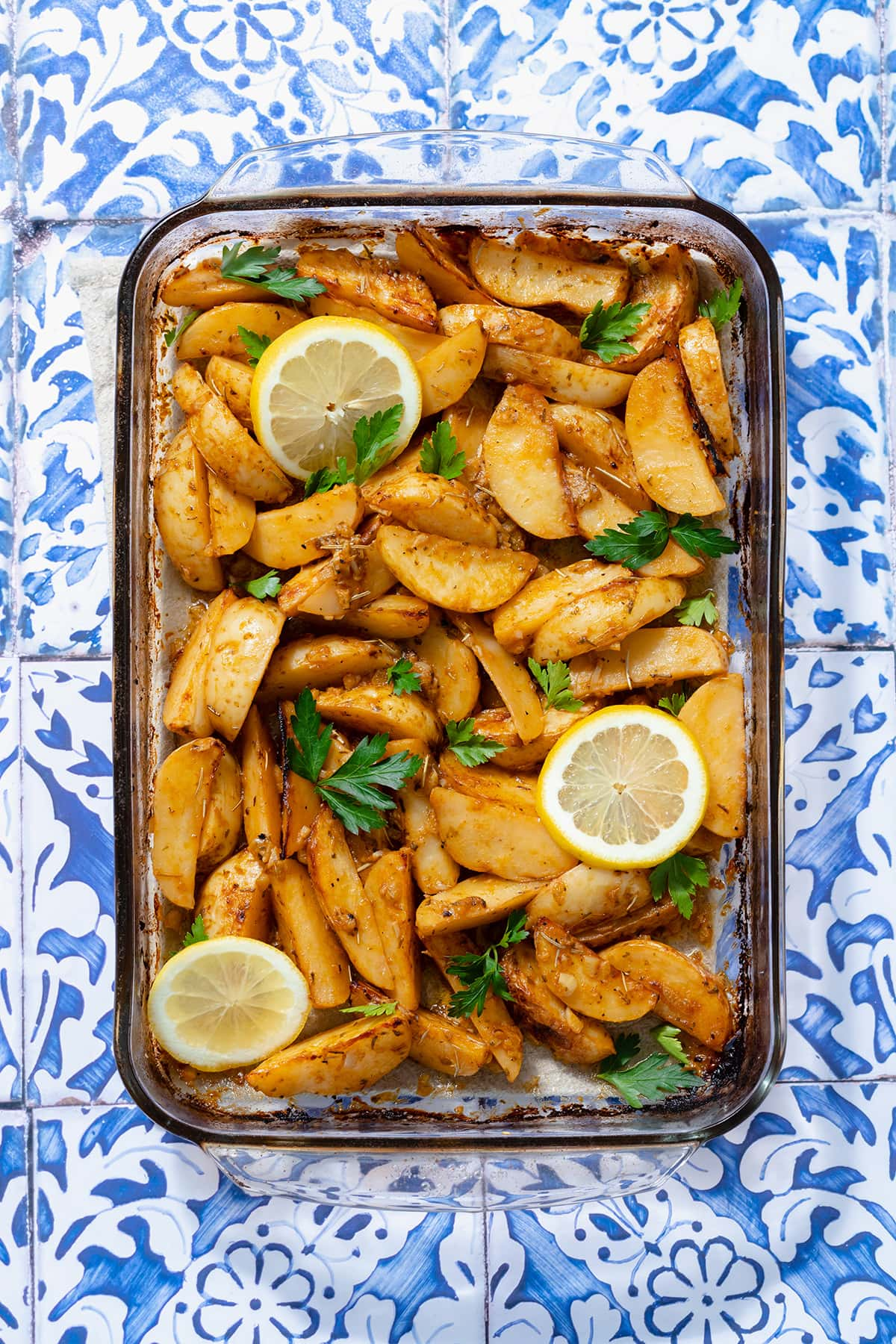 A photo of Mediterranean Potatoes garnished with three slice of lemon and chopped parsley. Blue tile background.
