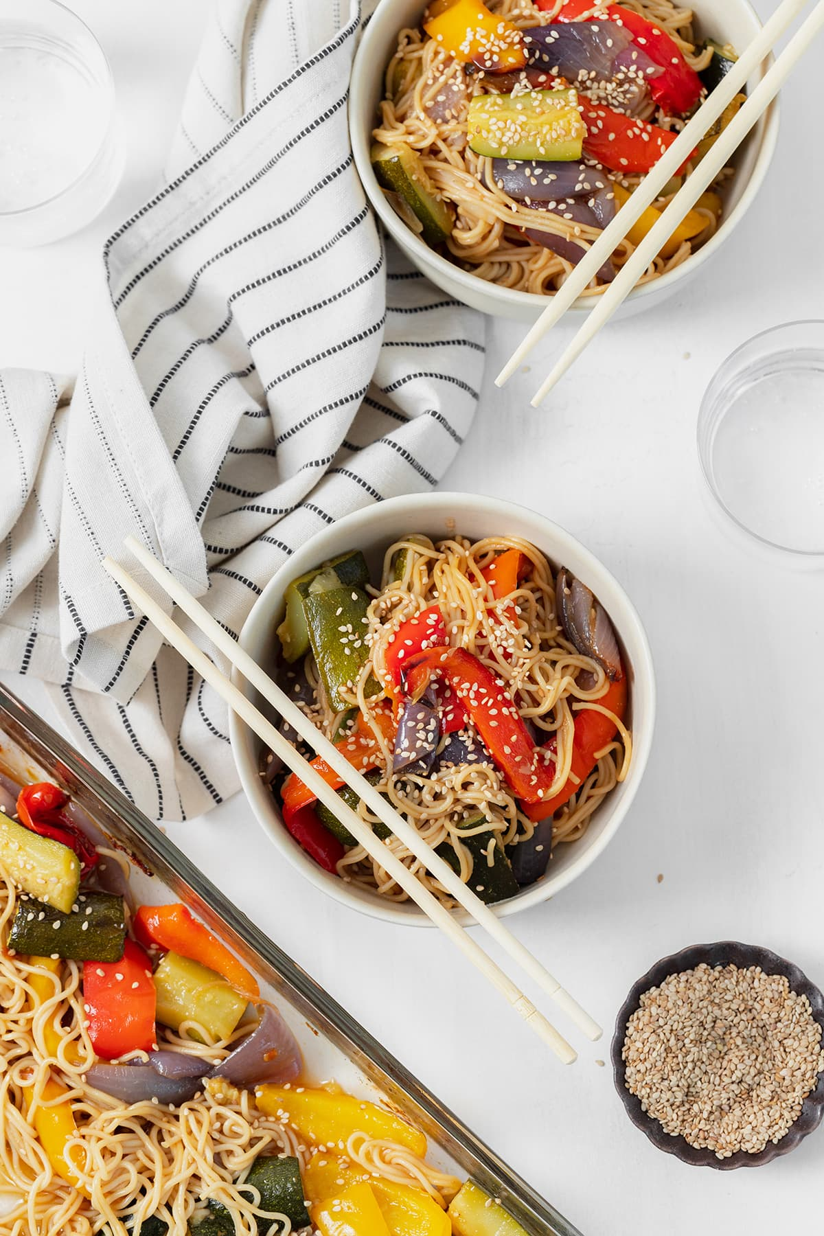 Gluten-free ramen noodle stir fry in two white bowls with chopsticks resting on the left side of the bowls. striped white and black napkin in the top left corner.