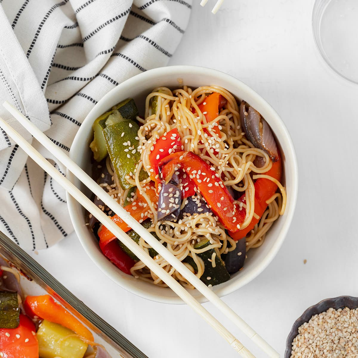 Gluten-free ramen noodle stir fry in a white bowl with chopsticks resting on the left side of the bowl. striped white and black napkin in the top left corner.