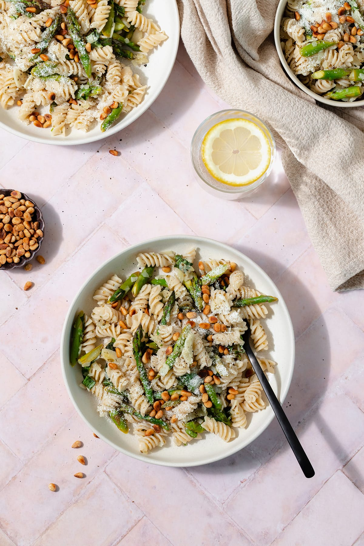 A low light green bowl with asparagus pasta and a black fork on a light pink tile background. Two more bowls, a little bowl with toasted pine nuts, and a glass of water with a lemon slice in the background.