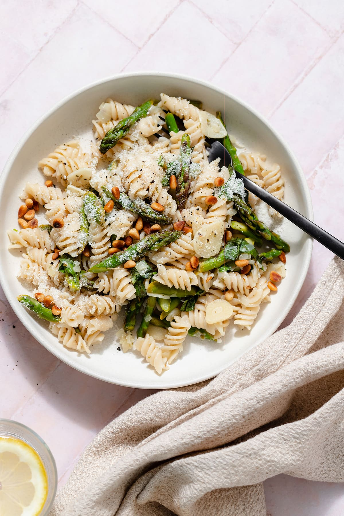 Asparagus pasta with toasted pine nuts and fresh basil on a light green low bowl with a black fork in the bowl. On a light pink tile background.