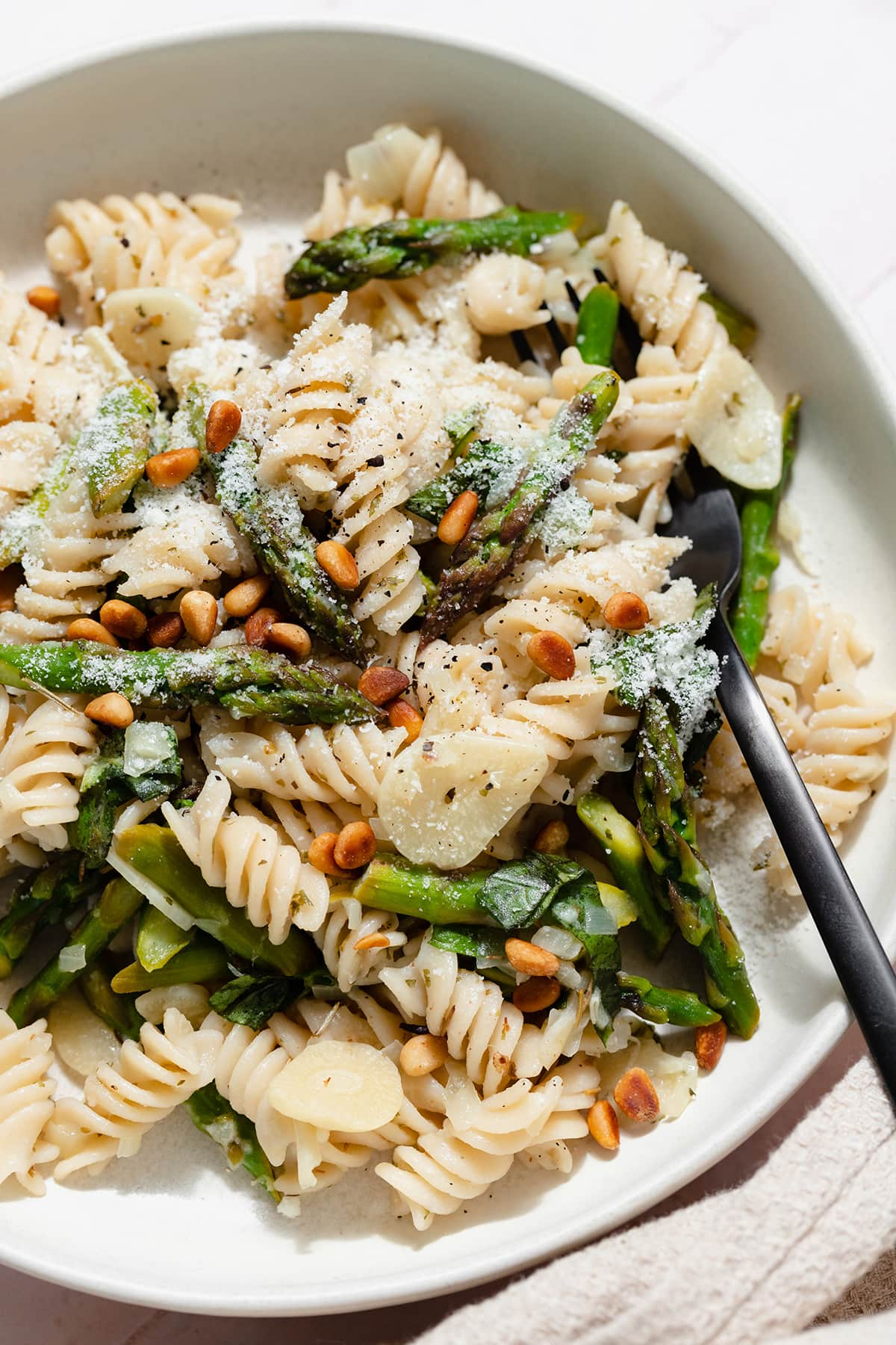 A close up of Asparagus pasta with toasted pine nuts and fresh basil on a light green low bowl with a black fork in the bowl. On a light pink tile background.