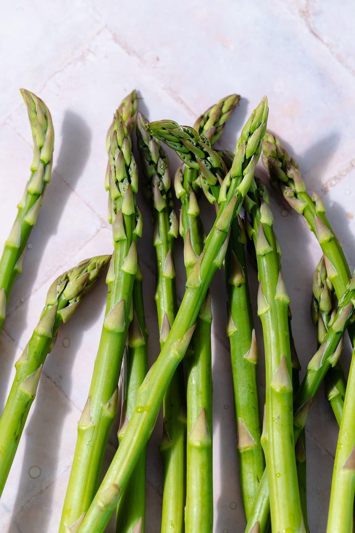 Fresh asparagus spears on pink tile background.