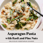 Asparagus pasta with toasted pine nuts and fresh basil on a light green low bowl with a black fork in the bowl. On a light pink tile background. Title of the recipe written in the photo in black letters.