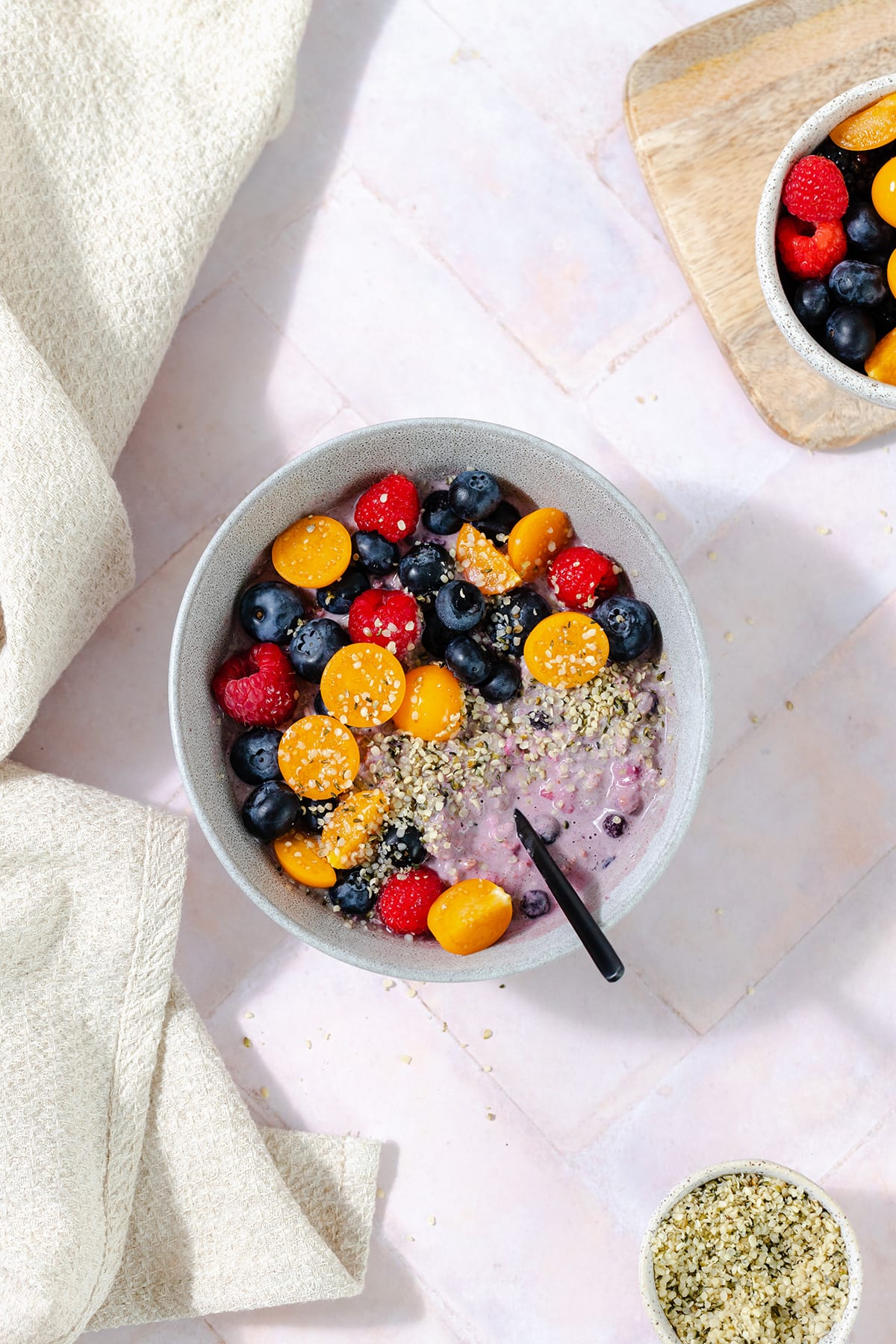 Overhead shot of blueberry overnight oats in a grey bowl topped with blueberries, raspberries, golden berries, and hemp seeds. Pink tile background.