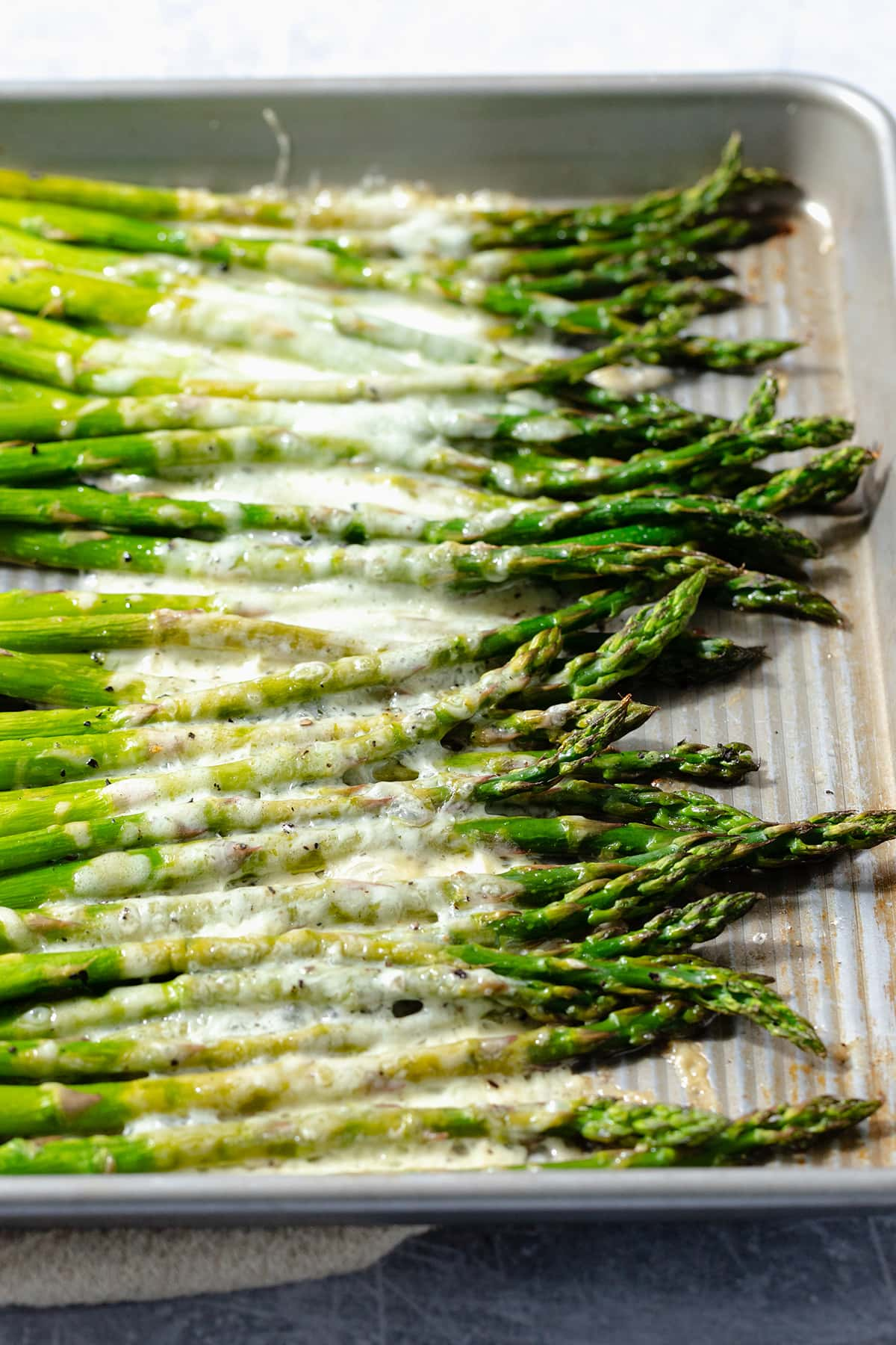 Roasted asparagus spears on a baking sheet with cheese sprinkled on that has melted in the oven.