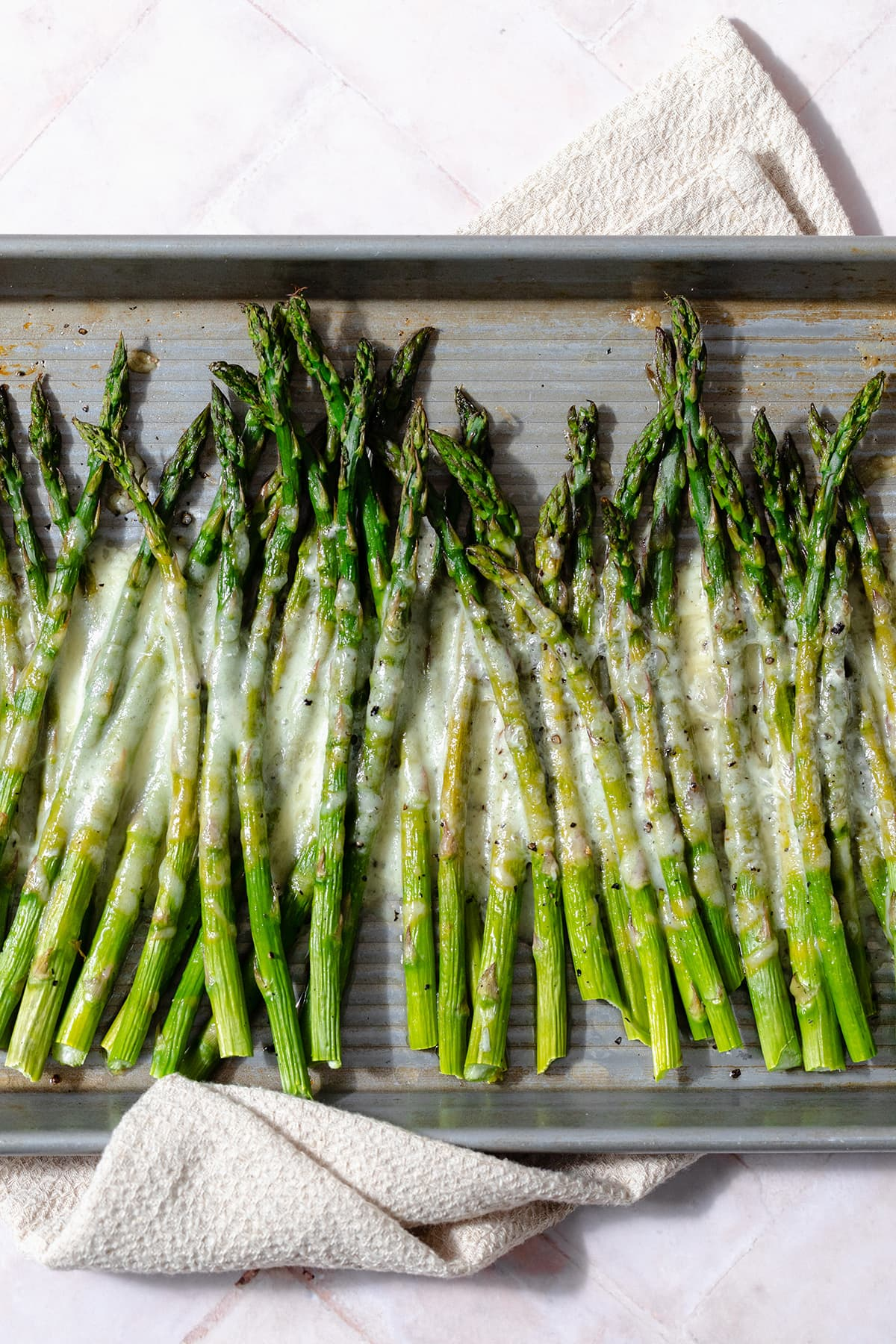 Baked asparagus spears on a sheet pan with cheese sprinkled on that has melted in the oven.