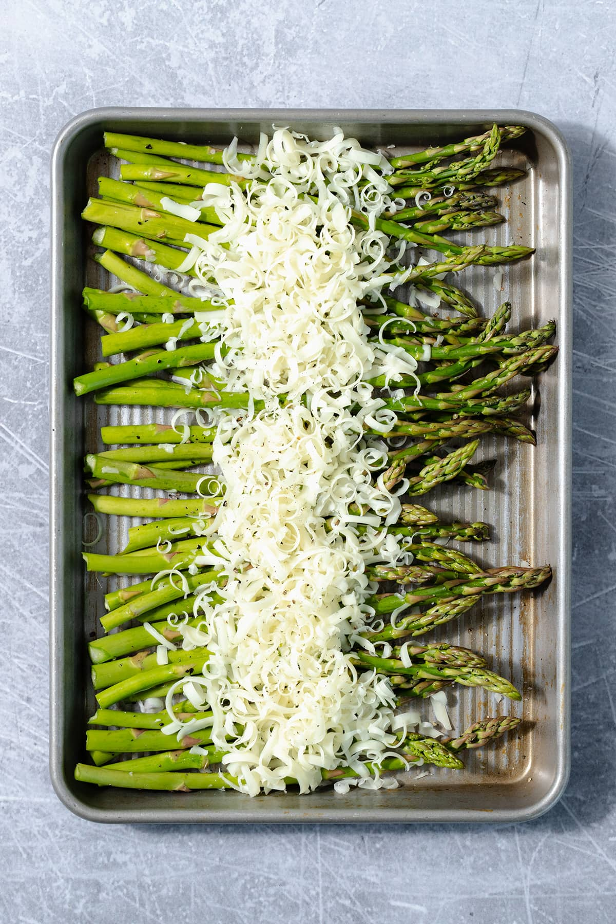 Fresh asparagus on a sheet pan sprinkled with grated cheese. Pan is on a scratched metal surface.