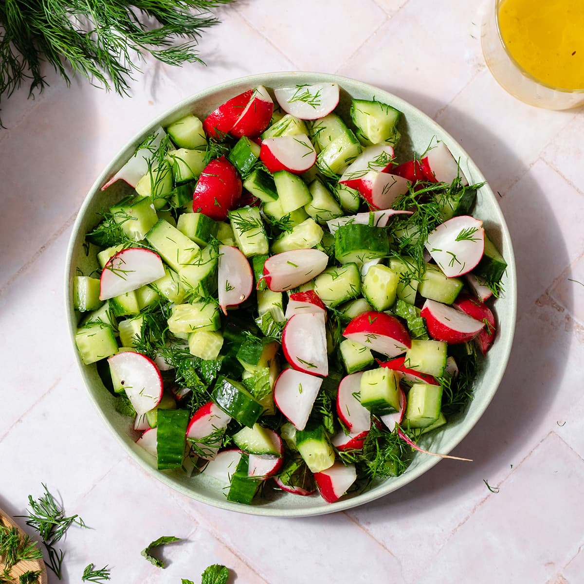 Cucumber Radish Salad in a shallow bowl on a light pink tile background. A bunch of fresh dill on the left side of the plate and the lemon vinaigrette on the right side of it.