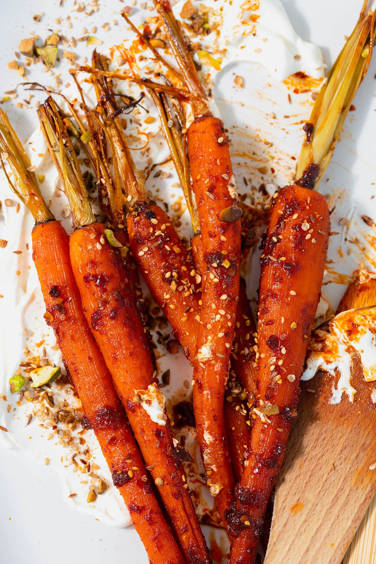 A tight close up of Harissa roasted carrots on a white serving platter with labneh spread under the carrots. Sprinkled with dukkah. Two wooden spoons messy with labneh and harissa leaning on the right edge of the platter. Plate on a white and turquoise tile table.