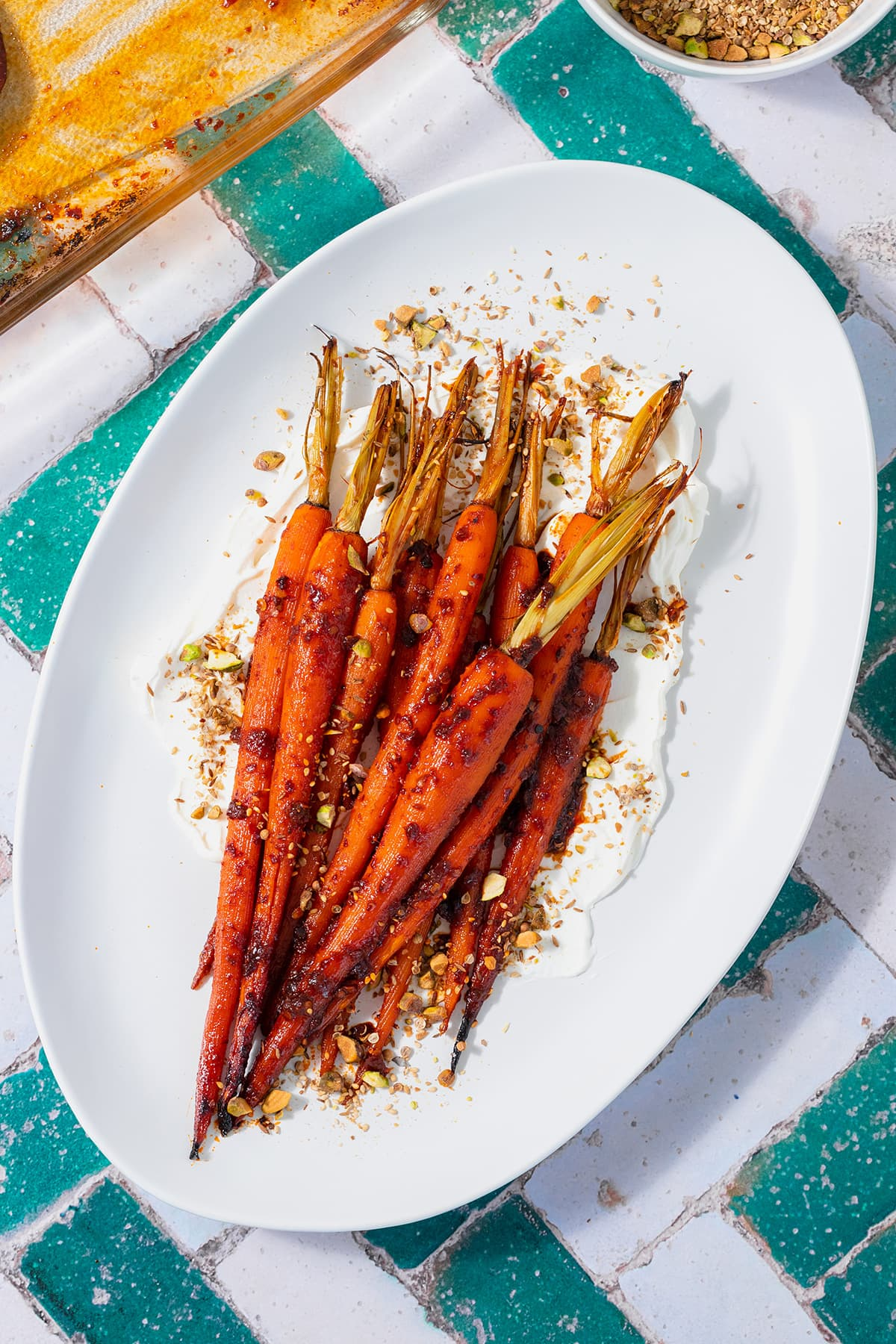 Harissa roasted carrots on a white serving platter with labneh spread under the carrots. Sprinkled with dukkah. Plate on a white and turquoise tile table.