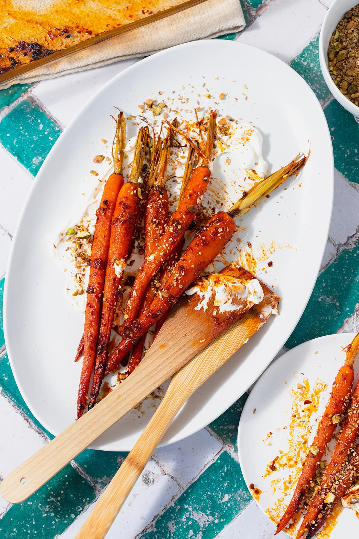 Harissa roasted carrots on a white serving platter with labneh spread under the carrots. Sprinkled with dukkah. Two wooden spoons messy with labneh and harissa leaning on the right edge of the platter. Plate on a white and turquoise tile table.