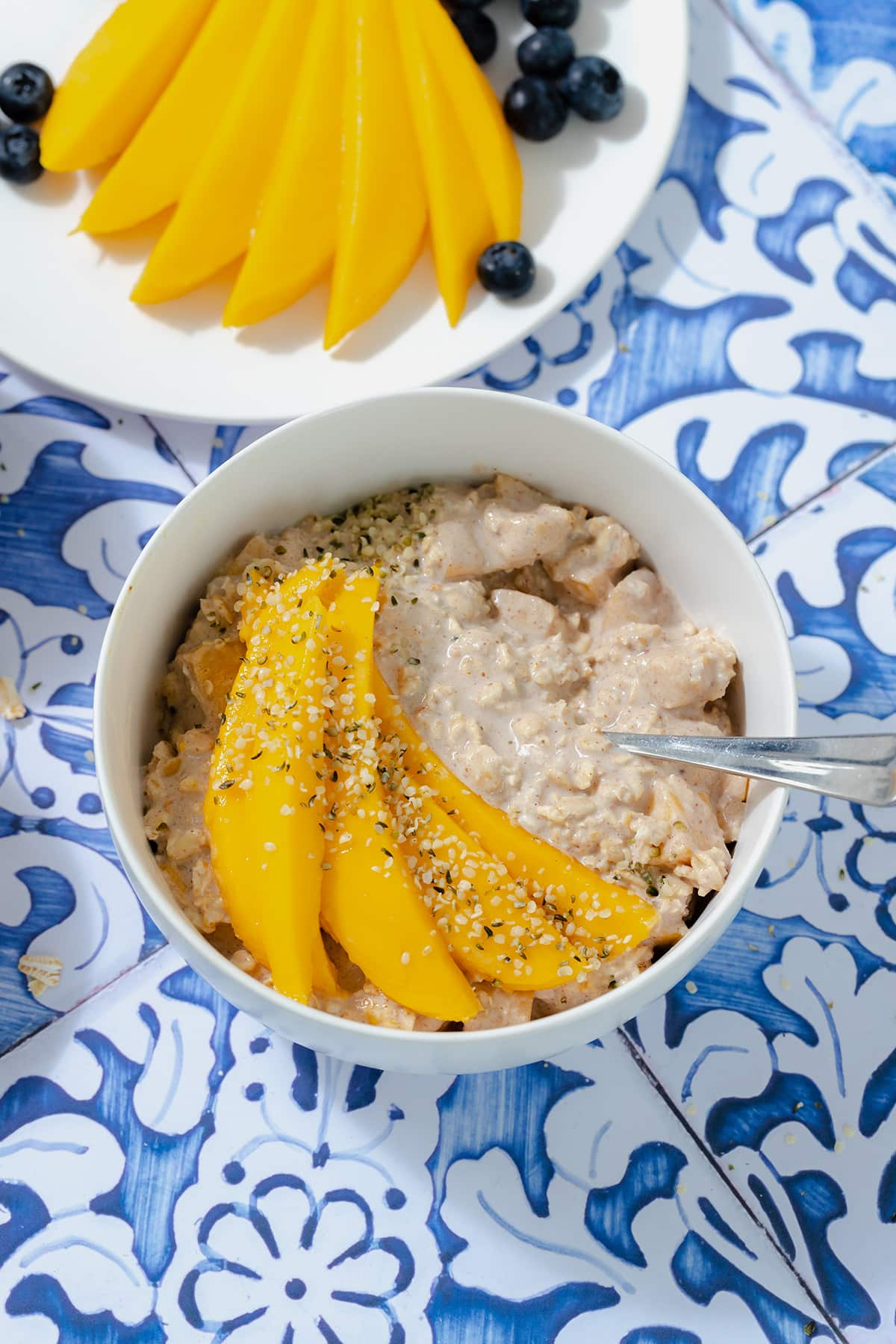Mango overnight oats in a white bowl on a blue tile background. Mango on a white plate in the top left corner.
