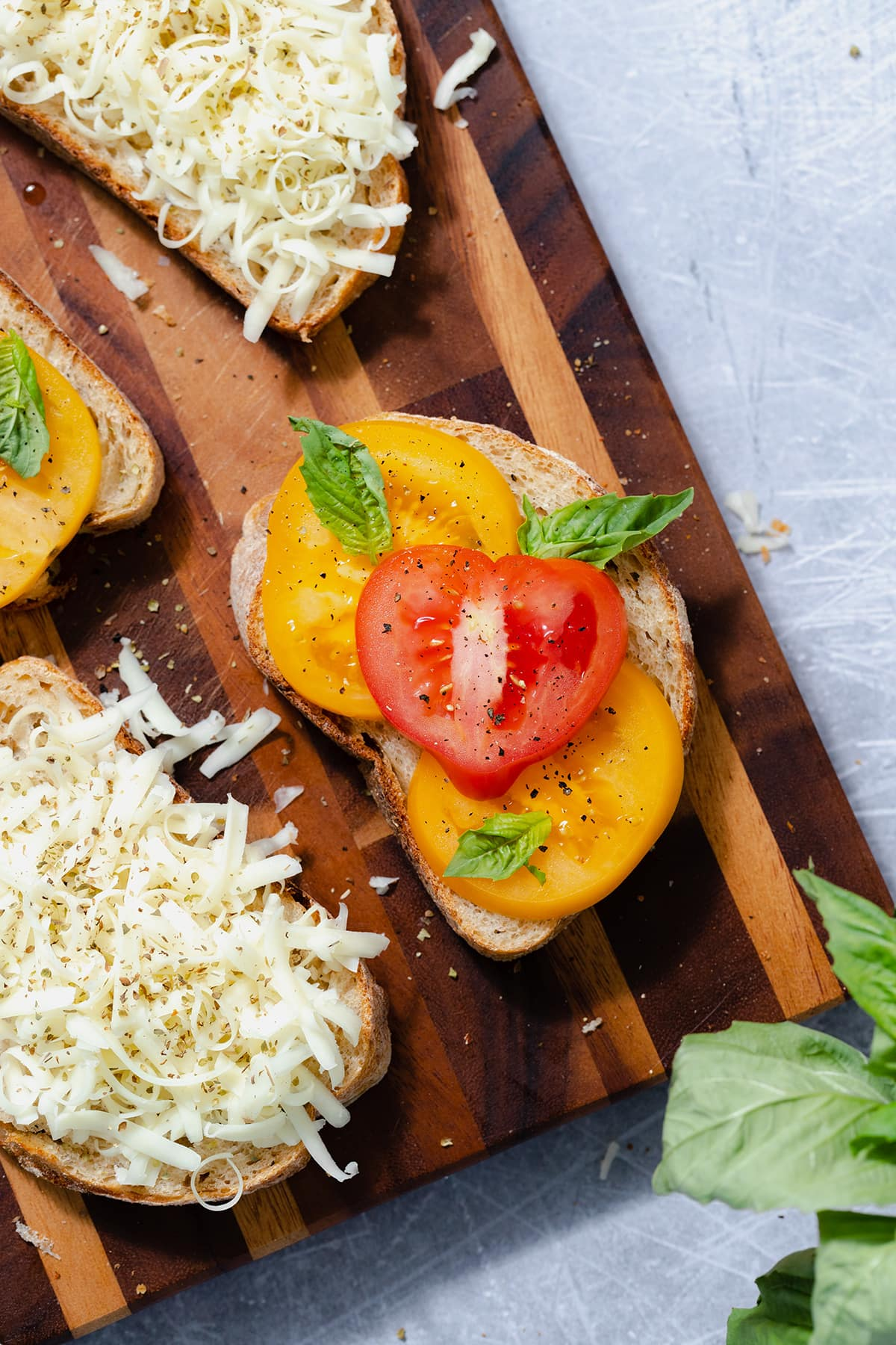 Four slices of bread on a cutting board. The main slice in focus in the middle, layered with sliced heirloom tomatoes and fresh basil. The slice on the bottom left layered with shredded cheese.