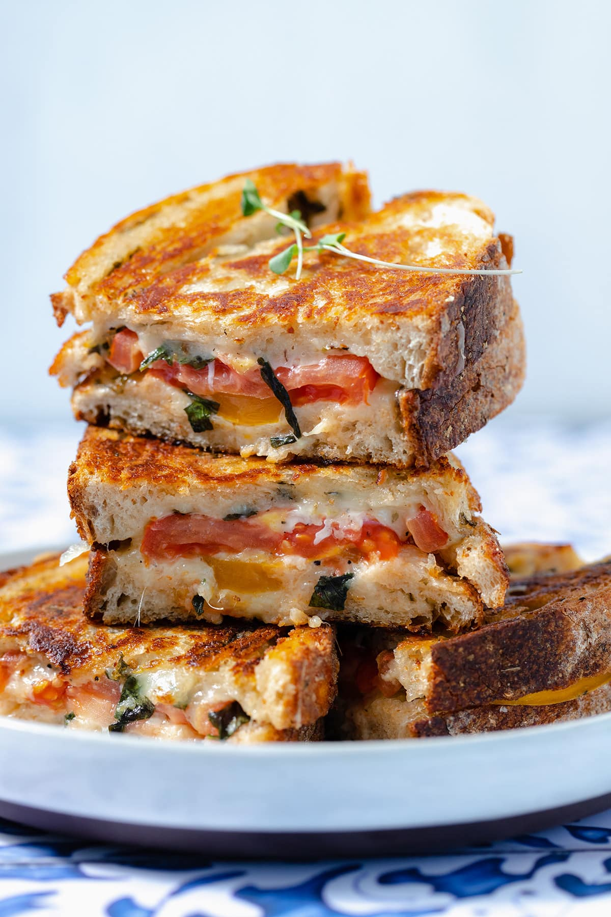 A close up of four tomato grilled cheese sandwiches stacked on top of each other.
