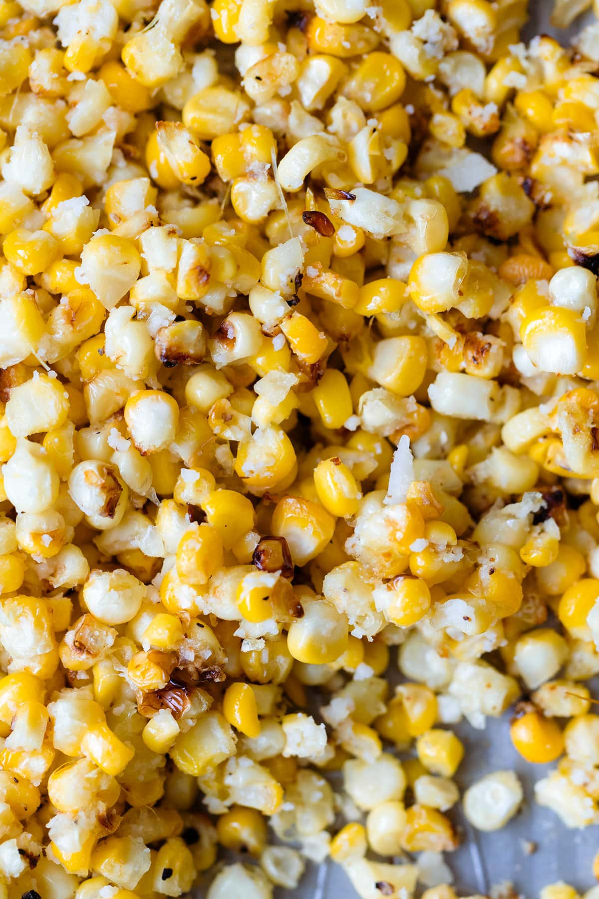 A close up of roasted corn kernels on a baking sheet, sprinkled with pecorino cheese