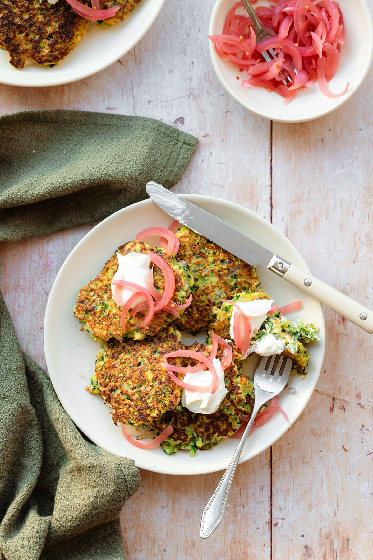 Zucchini fritters topped with pickled red onion and labneh on a white plate on a light wooden background with a green kitchen towel lying on the left. There is a fork and a knife on the plate with a cut up fritter.