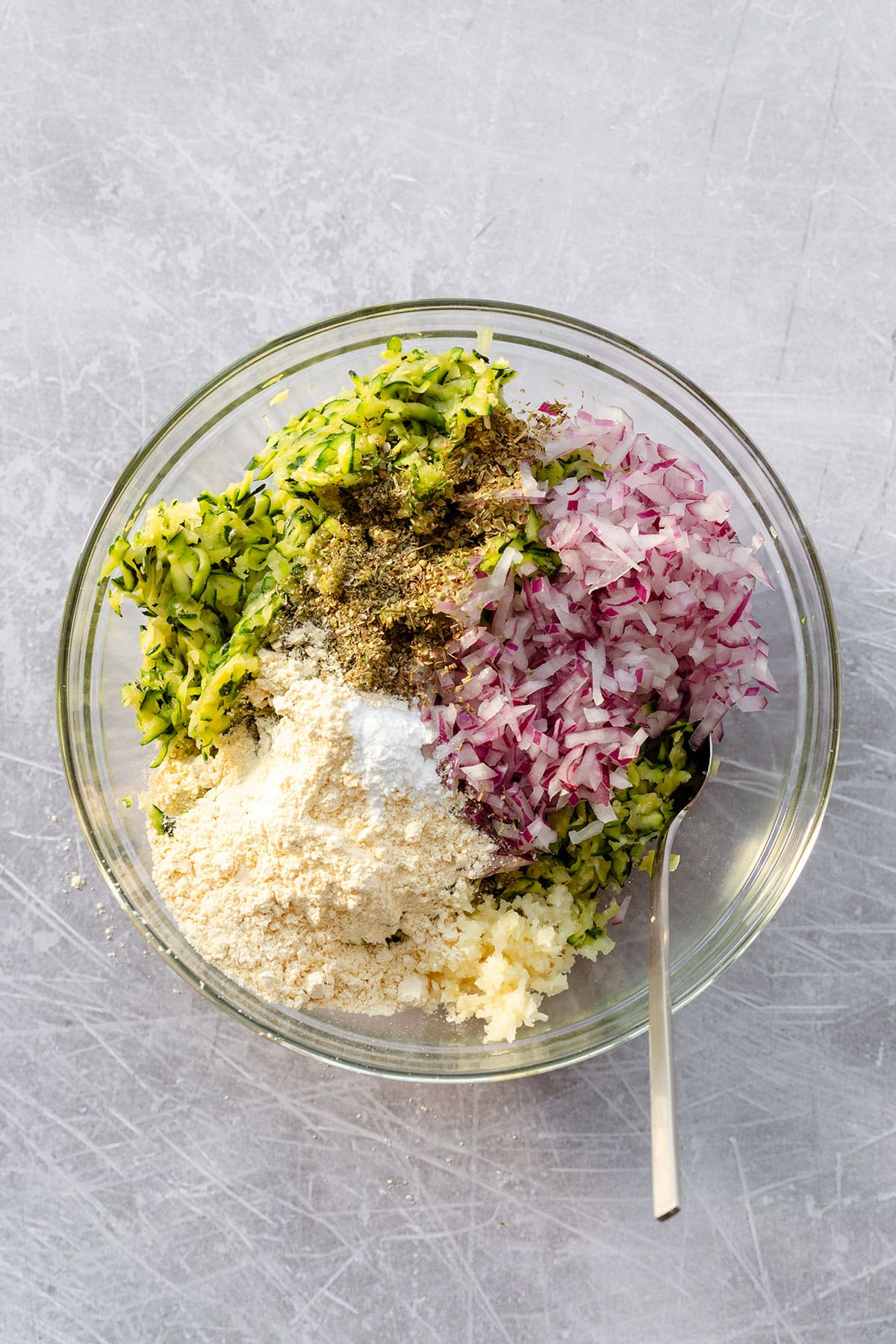 A glass bowl on a scratched steel background. In the bowl, there is grated zucchini chopped red onion, dried marjoram, and chickpea flour.