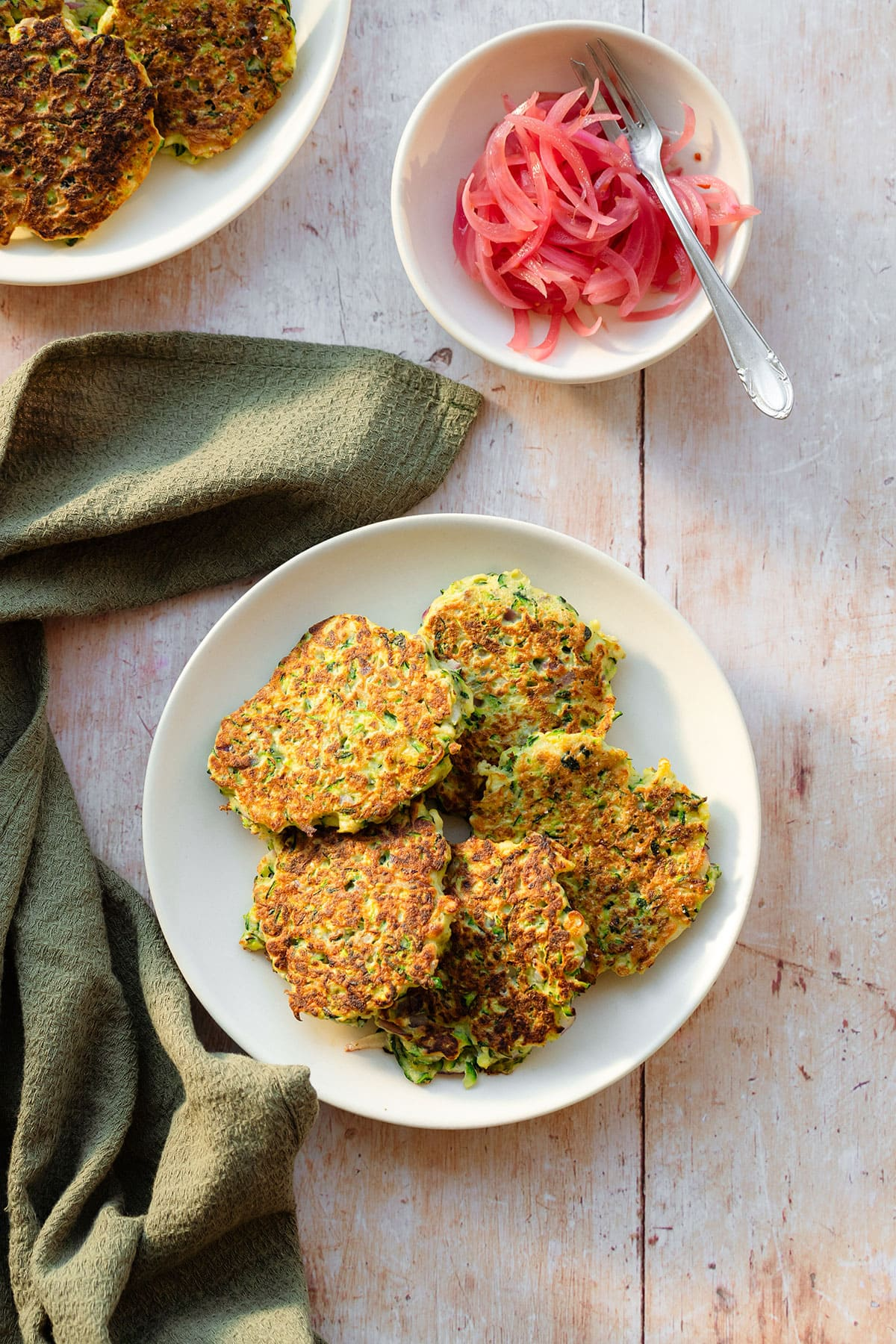Zucchini fritters on a white plate with pickled red onions served on the side on a small plate on a light wooden background with a green kitchen towel lying on the left and more fritters in the top left corner.