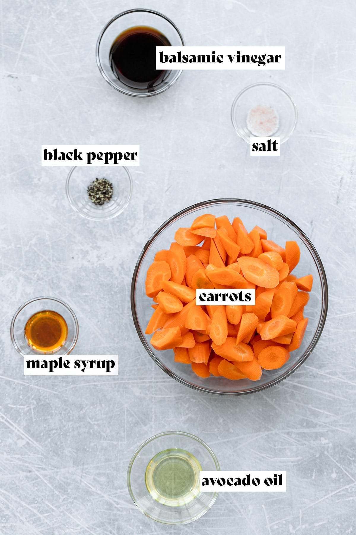 Ingredients needed to make balsamic roasted carrots on a light metal background.