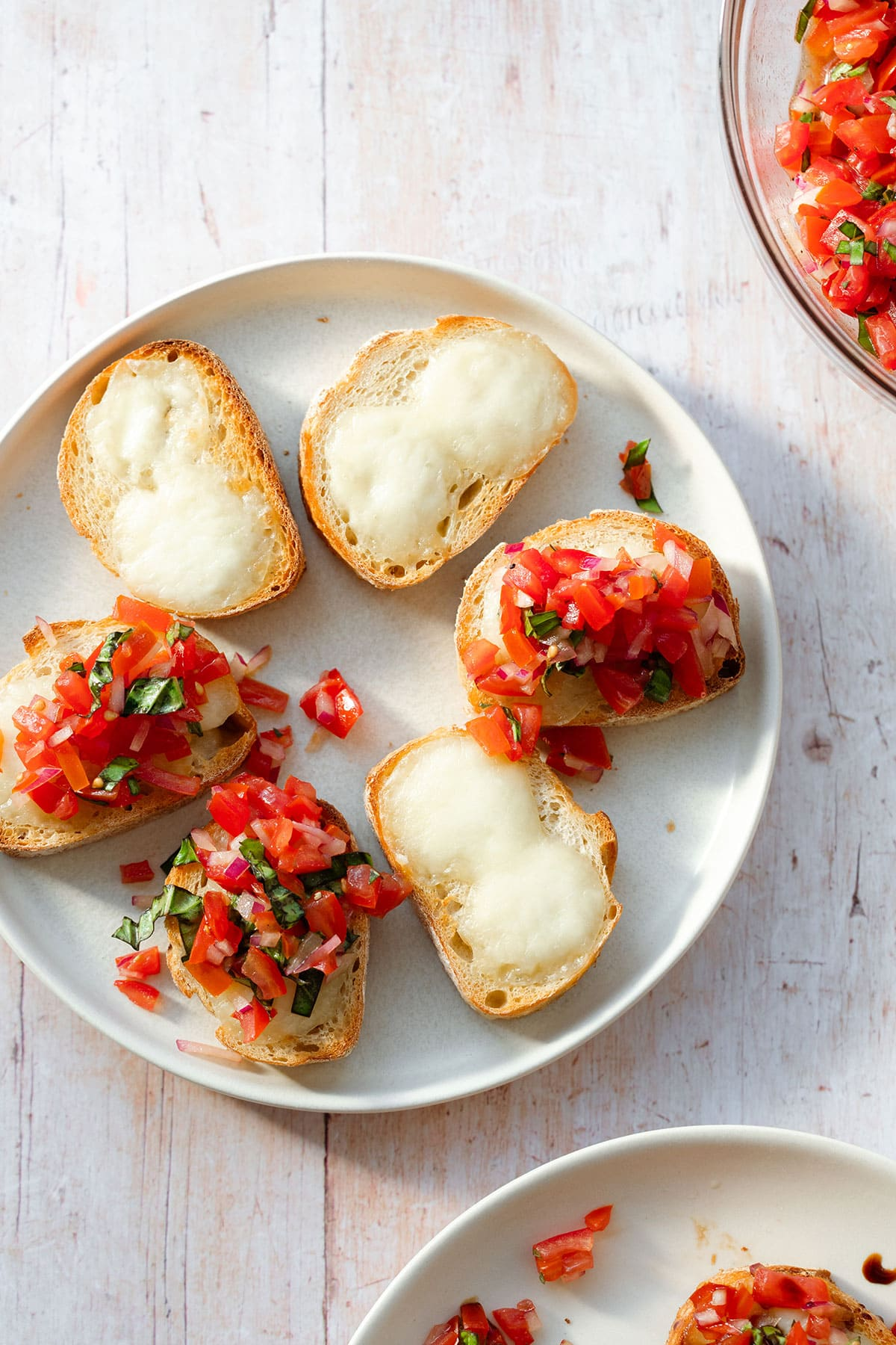 A beige plate with sliced toasted baguette with melted mozzarella cheese and tomatoes.