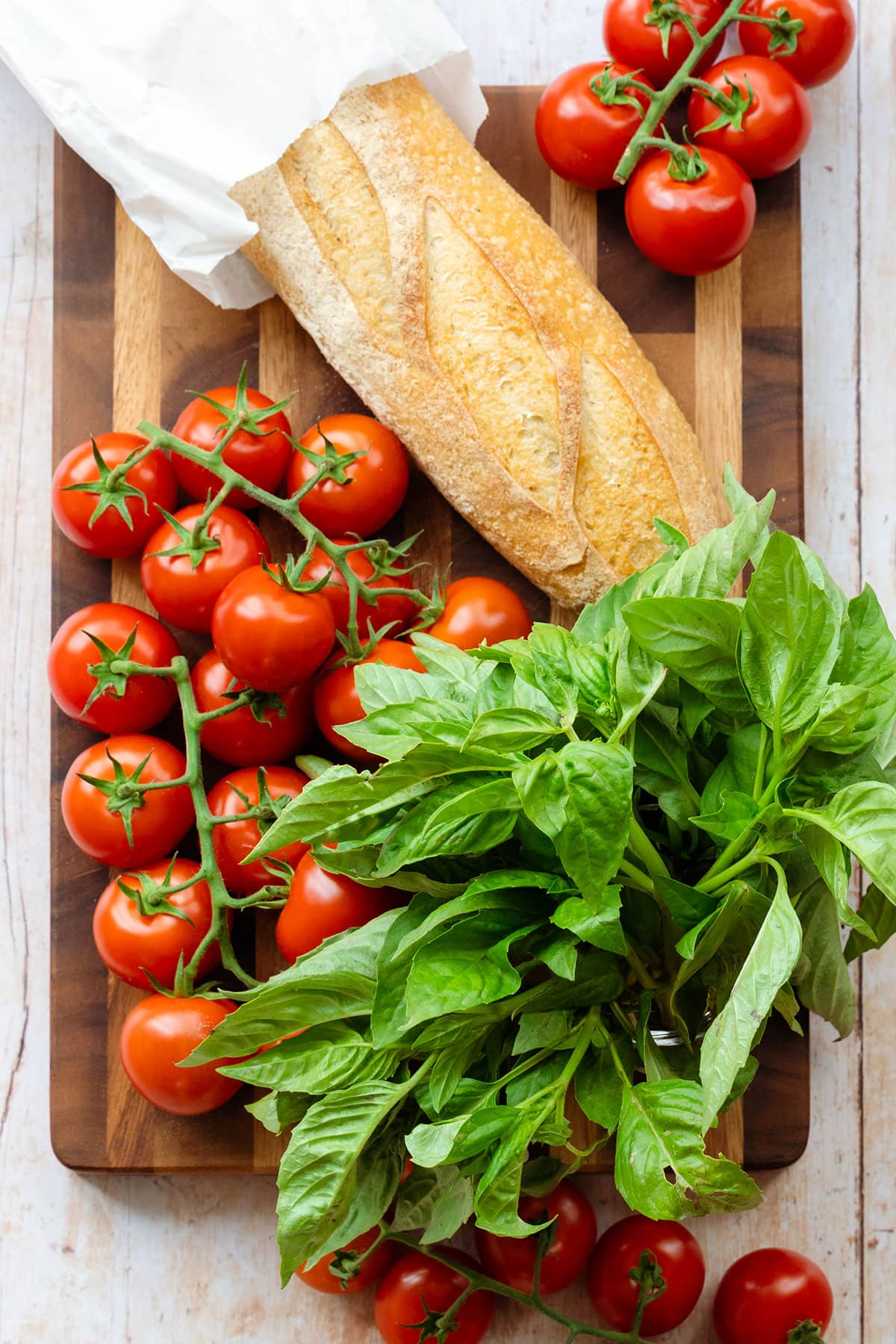 A fresh whole baguette, tomatoes on the wine, and fresh basil on a wooden cutting board.