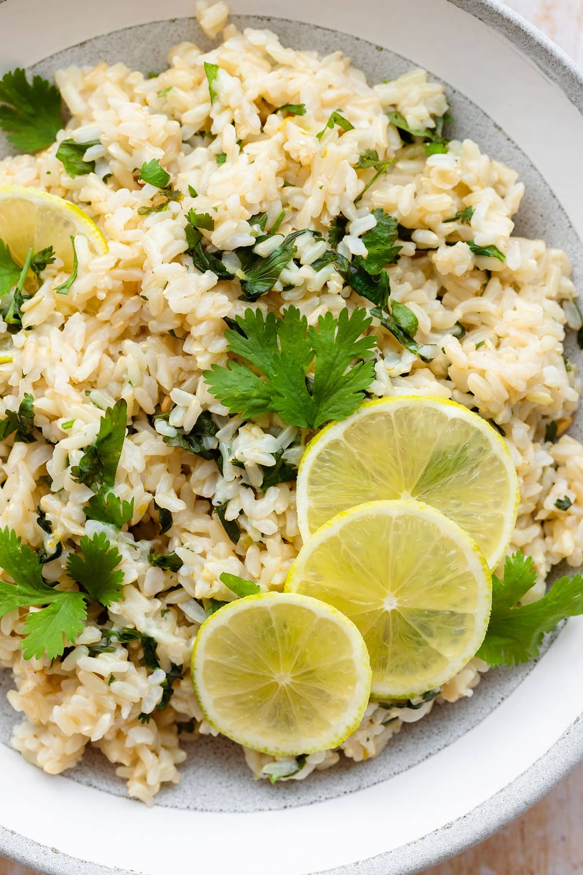 A close up of brown rice with cilantro and lime, decorated with lime slices. In a grey bowl with a white rim on a light wooden background.