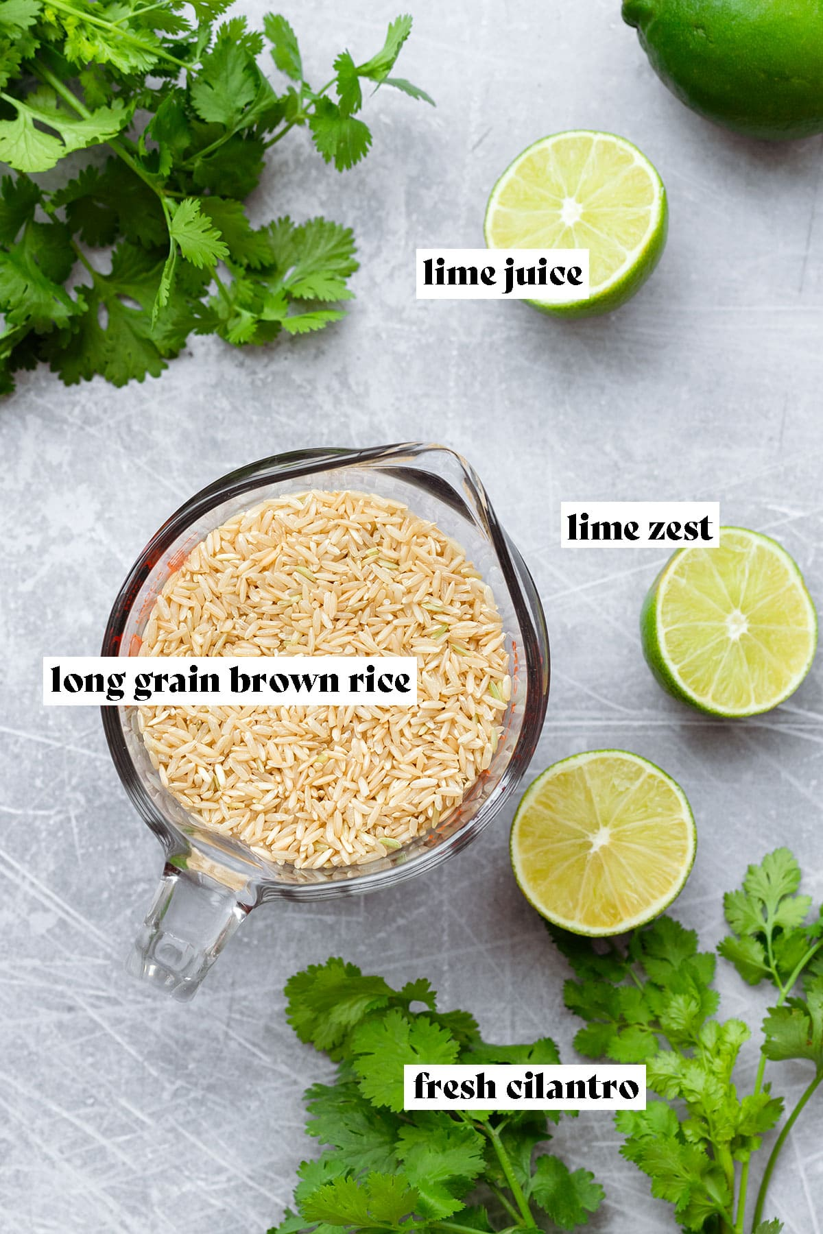 A photo of dry brown long-grain rice in a glass measuring cup with fresh lime and cilantro around on a steel background.