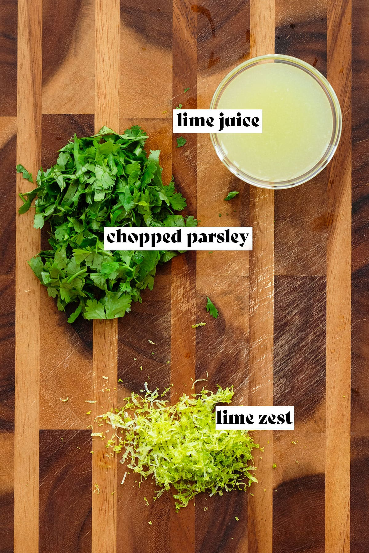 A photo of a wooden board with lime juice in a glass bowl in the top right, chopped fresh cilantro on the left, and fresh lime zest on the bottom middle.