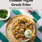 """Fries topped with diced red onion, fresh parsley, and tzatziki sauce on the side. One fry is dipped in the sauce. in beige shallow bowl on a wooden serving plate on a green and white tile background. There are bowls with extra toppings around. There is a text that says """"Loaded Vegan Greek Fries with red onion and parsley""""."""