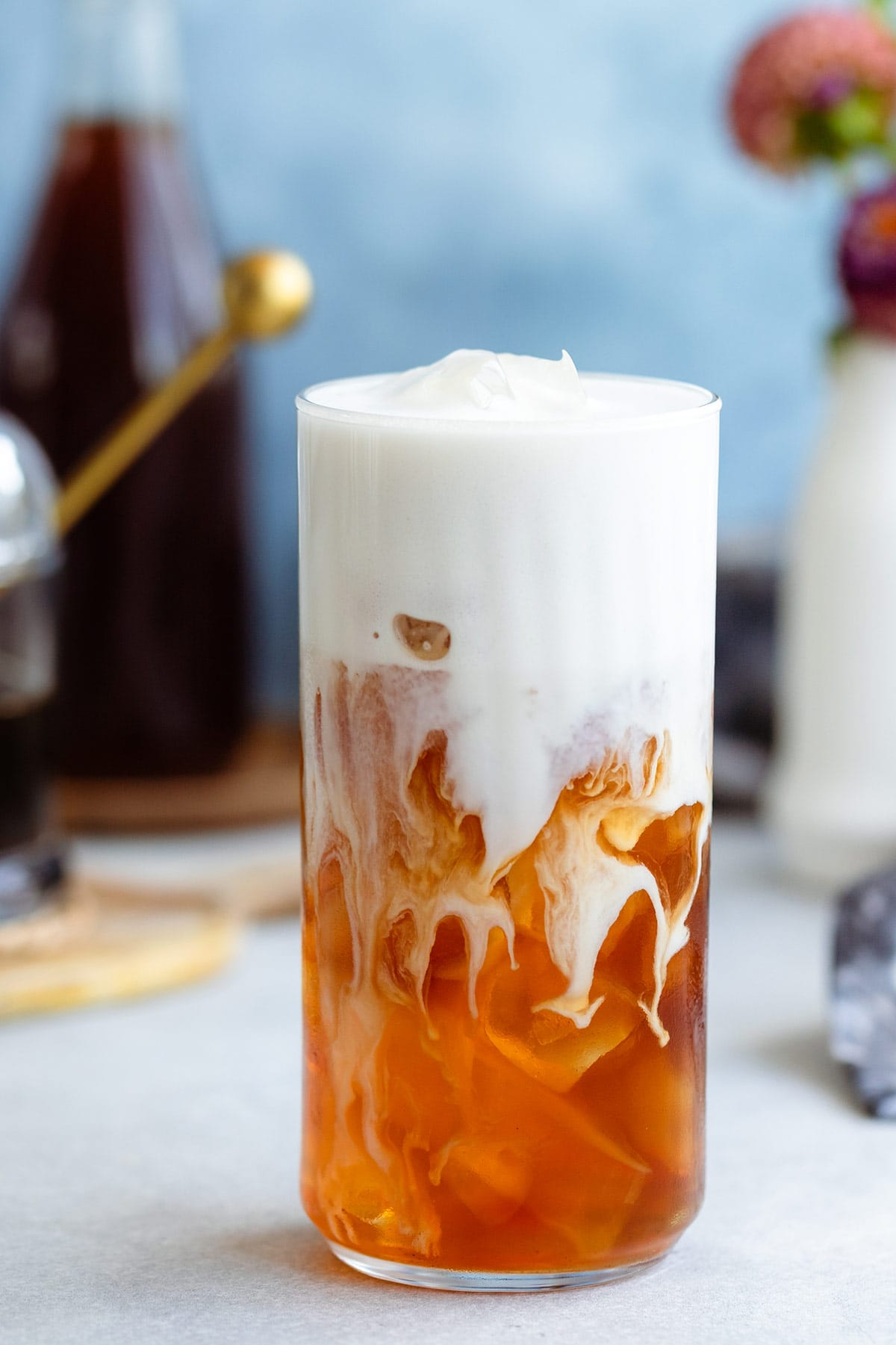 Earl grey in a tall glass with ice and frothy milk on top slowly blending together.