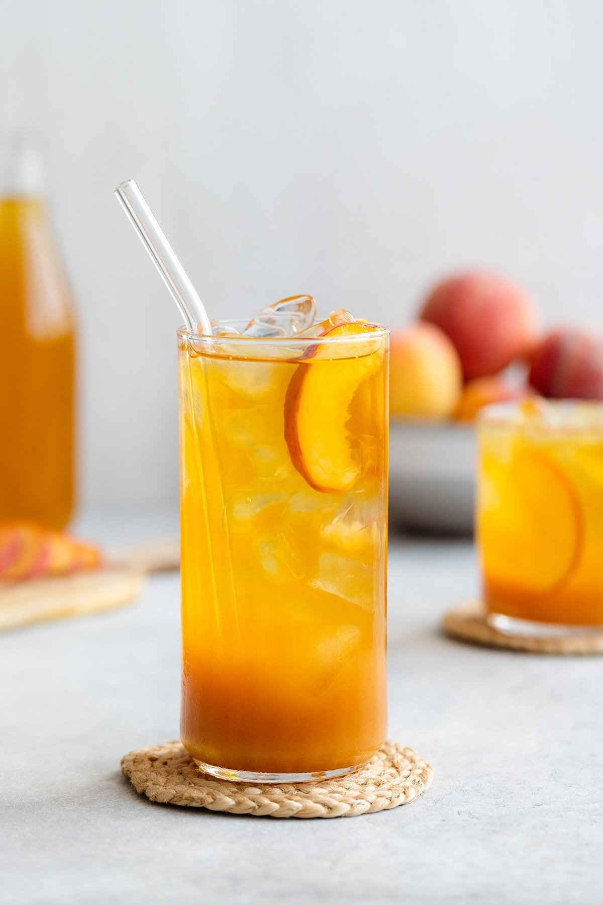 Iced tea in a tall and short glass with ice and peach slices on a light grey background with more peaches in a bowl in the back.