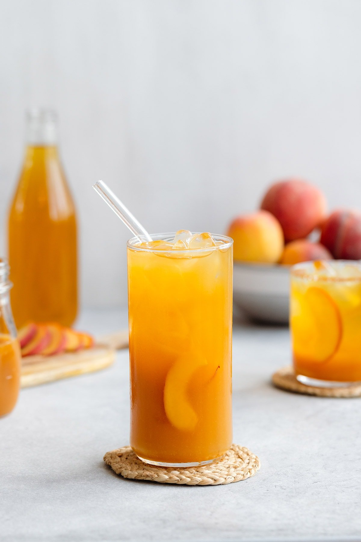 Iced tea in a tall glass with ice and peach slices on a light grey background with more peaches in a bowl in the back.