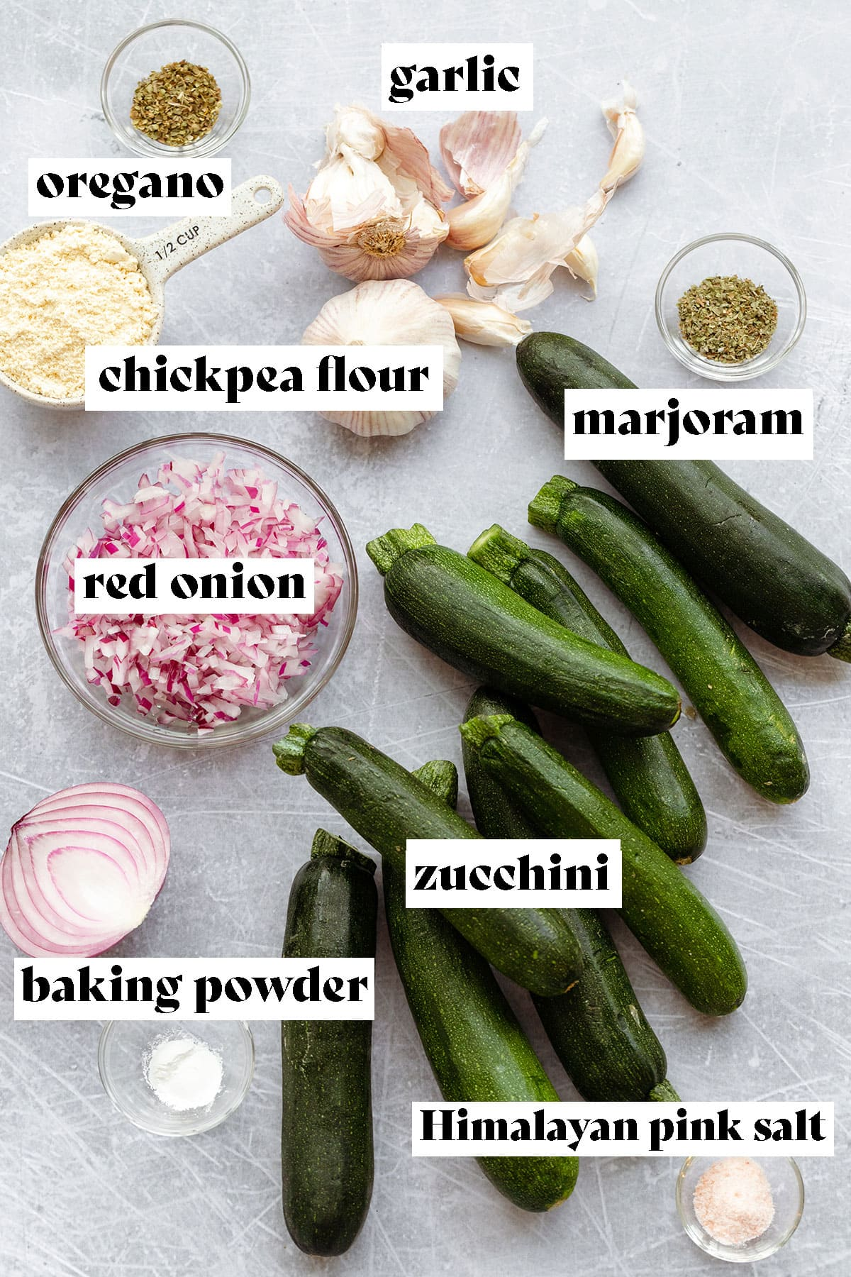 Ingredients to make zucchini fritters layed out on a steel background. Zucchini, red onion, baking powder, himalayan pink salt, marjoram, chickpea flour, oregano, and garlic.