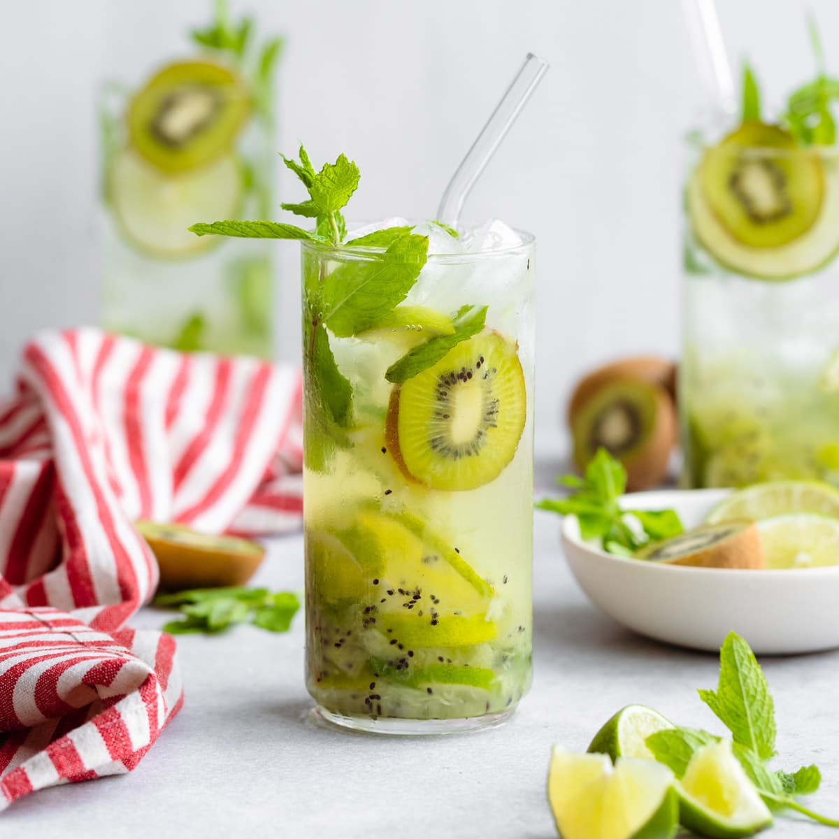Three Kiwi Mojitos in tall glasses garnished with lime and kiwi slices. On grey background with a striped red and white kitchen towel on the left.