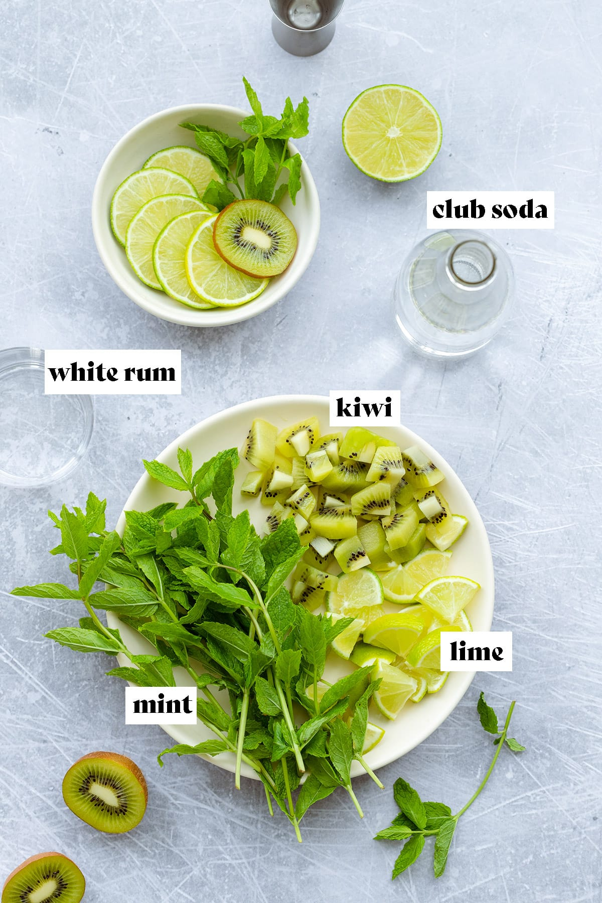 Ingredients for the cocktail laid out on a scratched metal background. There is chopped kiwi, lime, fresh mint, club soda, and white rum.