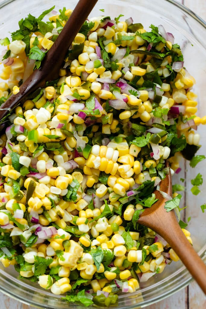 A close up of a glass bowl with Roasted Chili Corn salsa with two wooden mixing spoons on a light wooden backgrond.