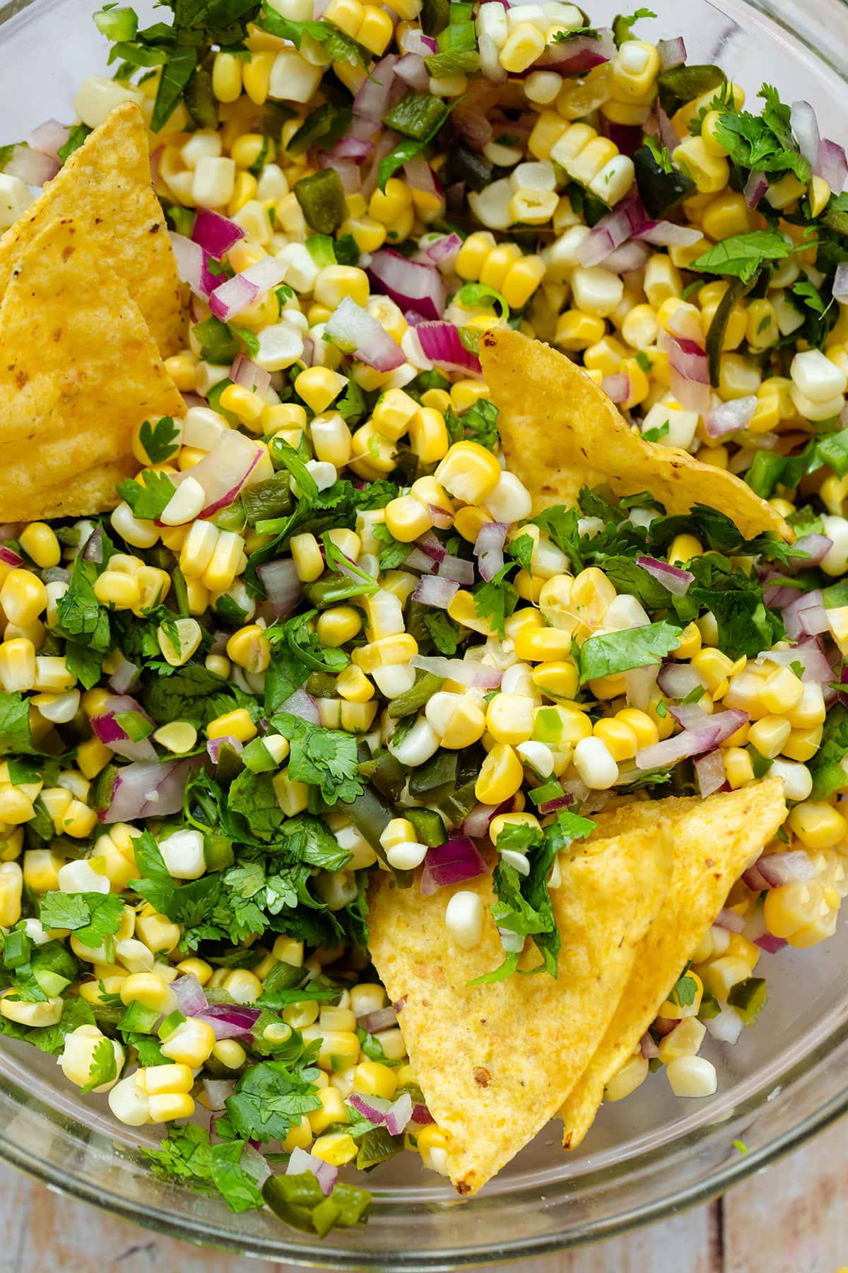A close up of a glass bowl with Chili Corn salsa on a light wooden backgrond.