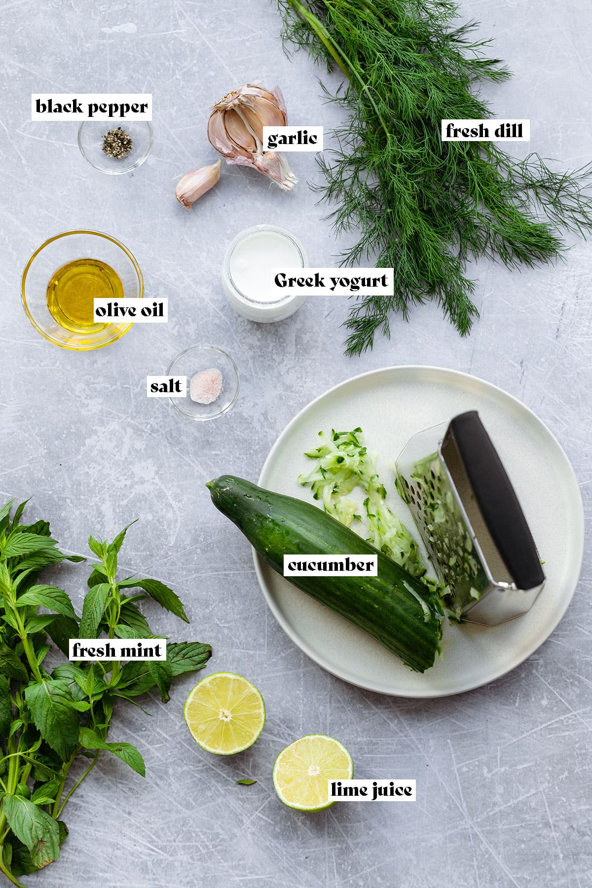 A photo of all the tzatziki ingredients laid out on a metal background. Fresh dill, mint, cucumber, limes, olive oil, greek yogurt, garlic, black pepper, and salt.