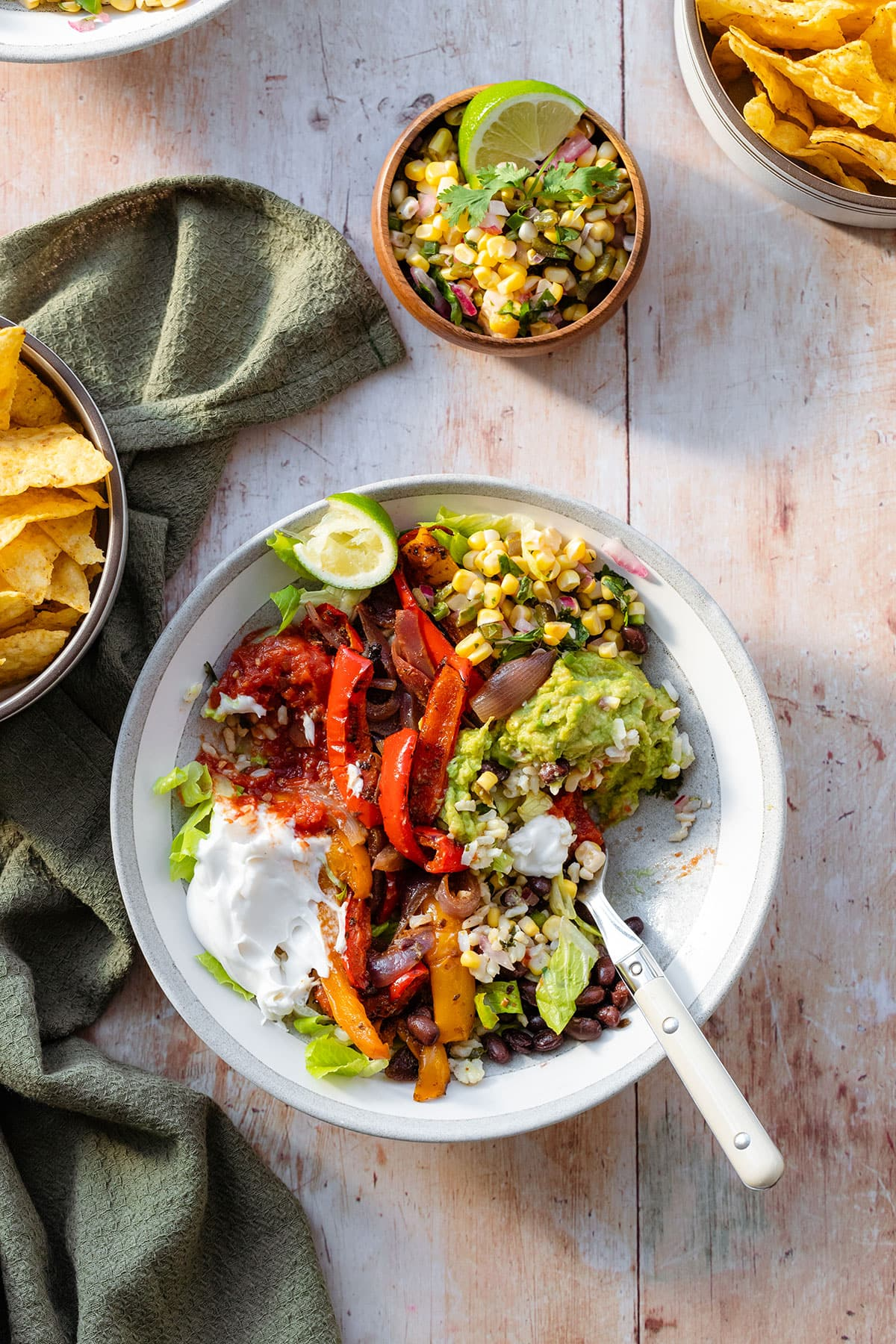A photo of veggie burrito bowls in a grey bowls with a white rim on a light wooden background with a green kitchen towel on the left and a small bowl with corn salsa above the bowl in the middle. In the bowl there is brown rice, corn salsa, tomato salsa, sour cream, guacamole, black beans, and roasted peppers.