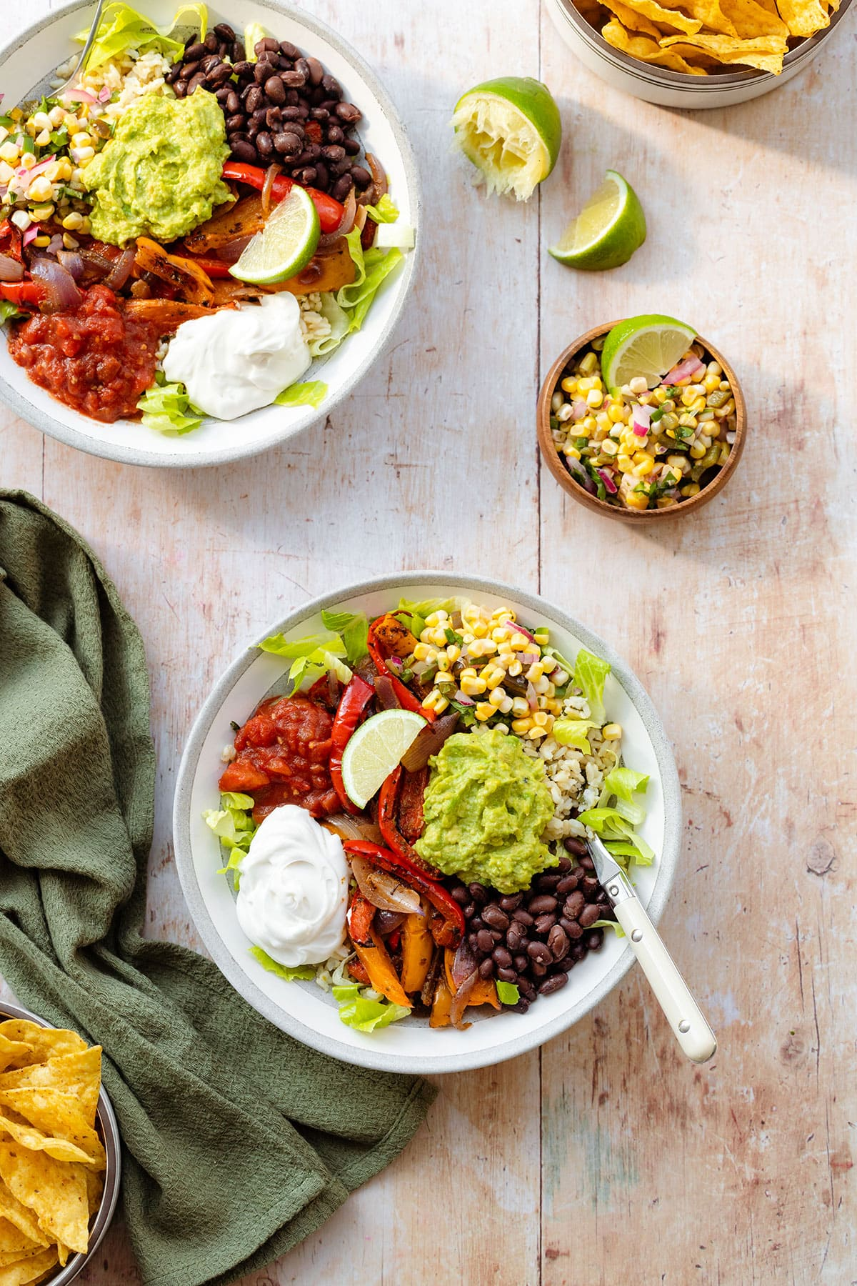 A photo of veggie burrito bowl in a grey bowl with a white rim on a light wooden background with a green kitchen towel on the left. In the bowl there is brown rice, corn salsa, tomato salsa, sour cream, guacamole, black beans, and roasted peppers.