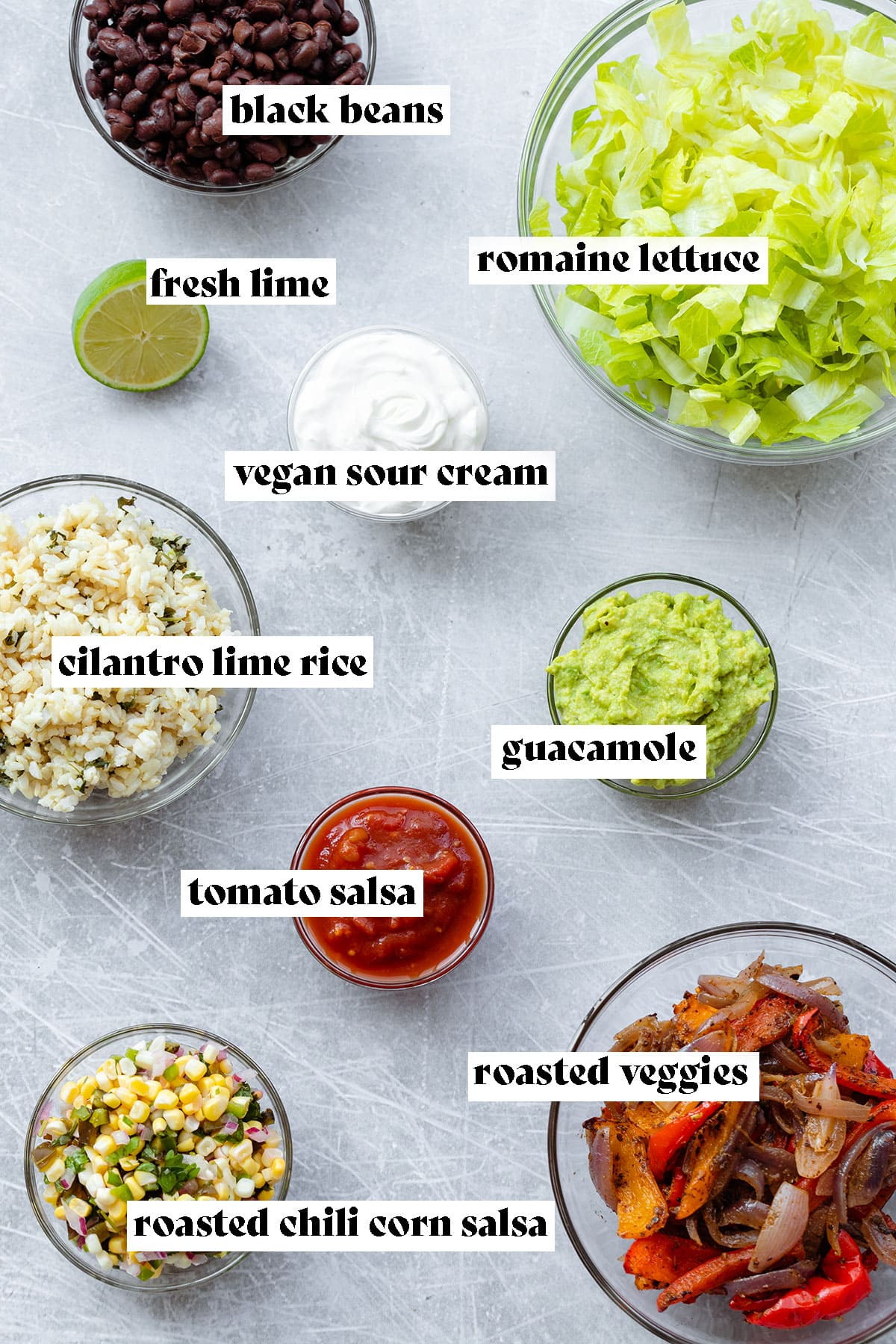 Ingredients in glass bowls on a steel background. Romaine lettuce, black beans, vegan sour cream, guacamole, cilantro lime rice, tomato salsa, roasted chili corn salsa, and roasted veggies.