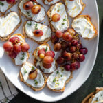 Crostini with goat cheese and roasted grapes on a white plate on a dark green background.